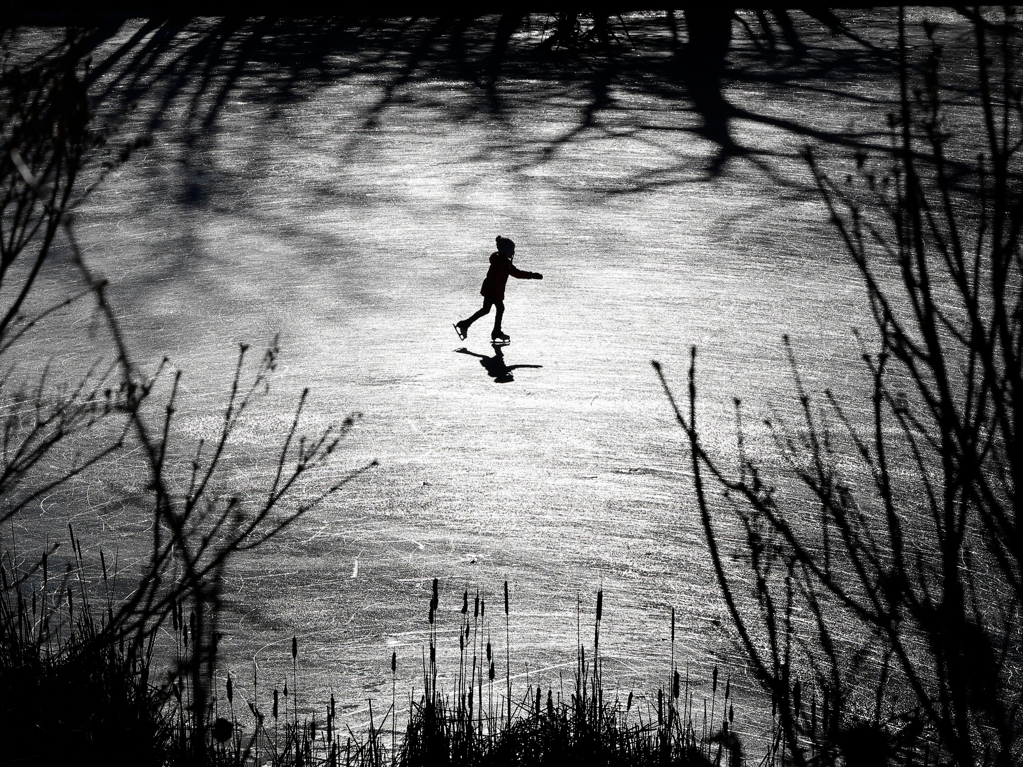 A girl skates across a frozen pond, Dec. 26, 2018, in Freeport, Maine.