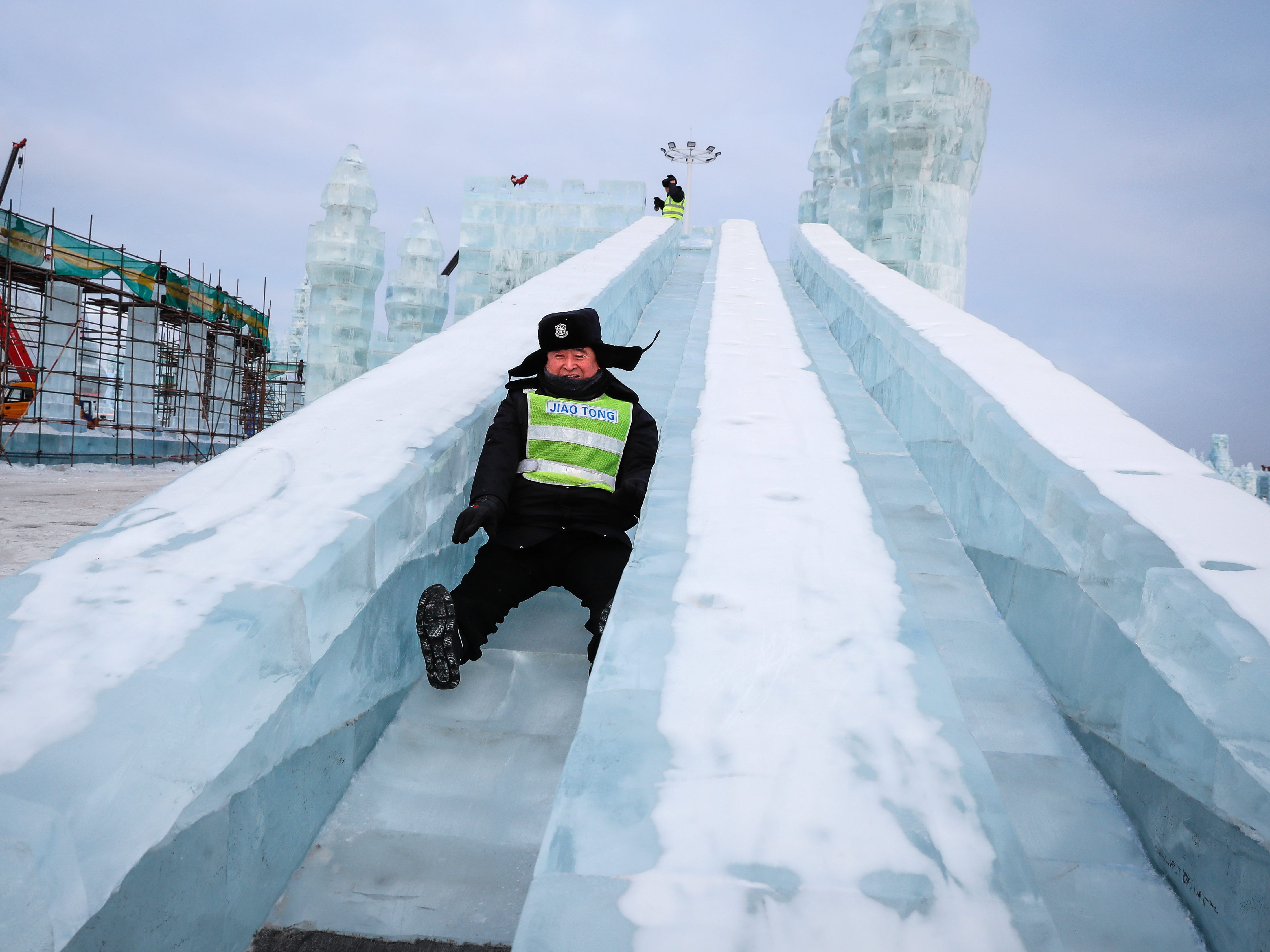 A security guard rides a slide of an ice sculpture at the Ice and Snow World during the annual Harbin International Ice and Snow Sculpture Festival.