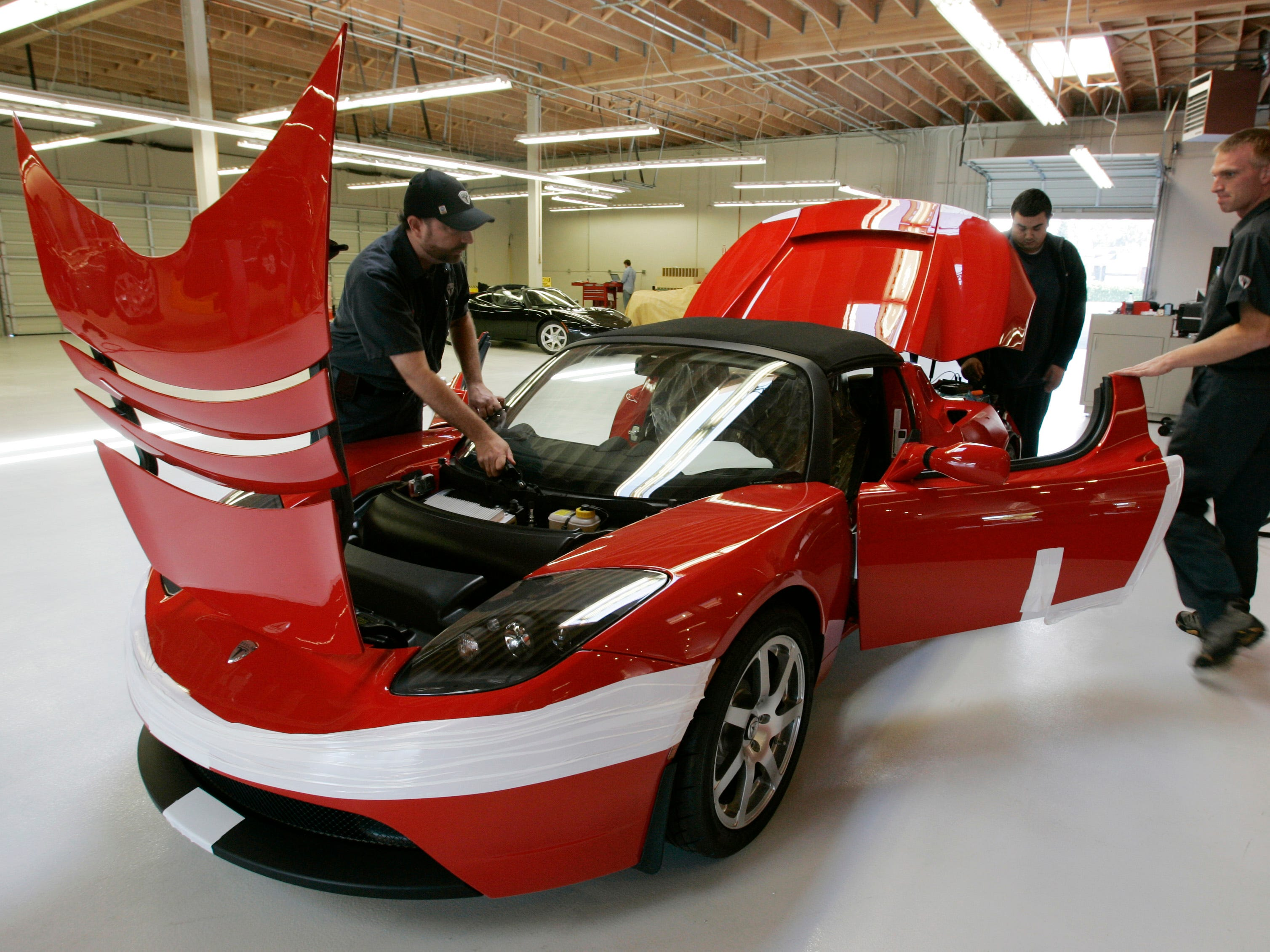 Workers assembly a Tesla Roadster at their showroom in Menlo Park, Calif. Sept. 16, 2008.
