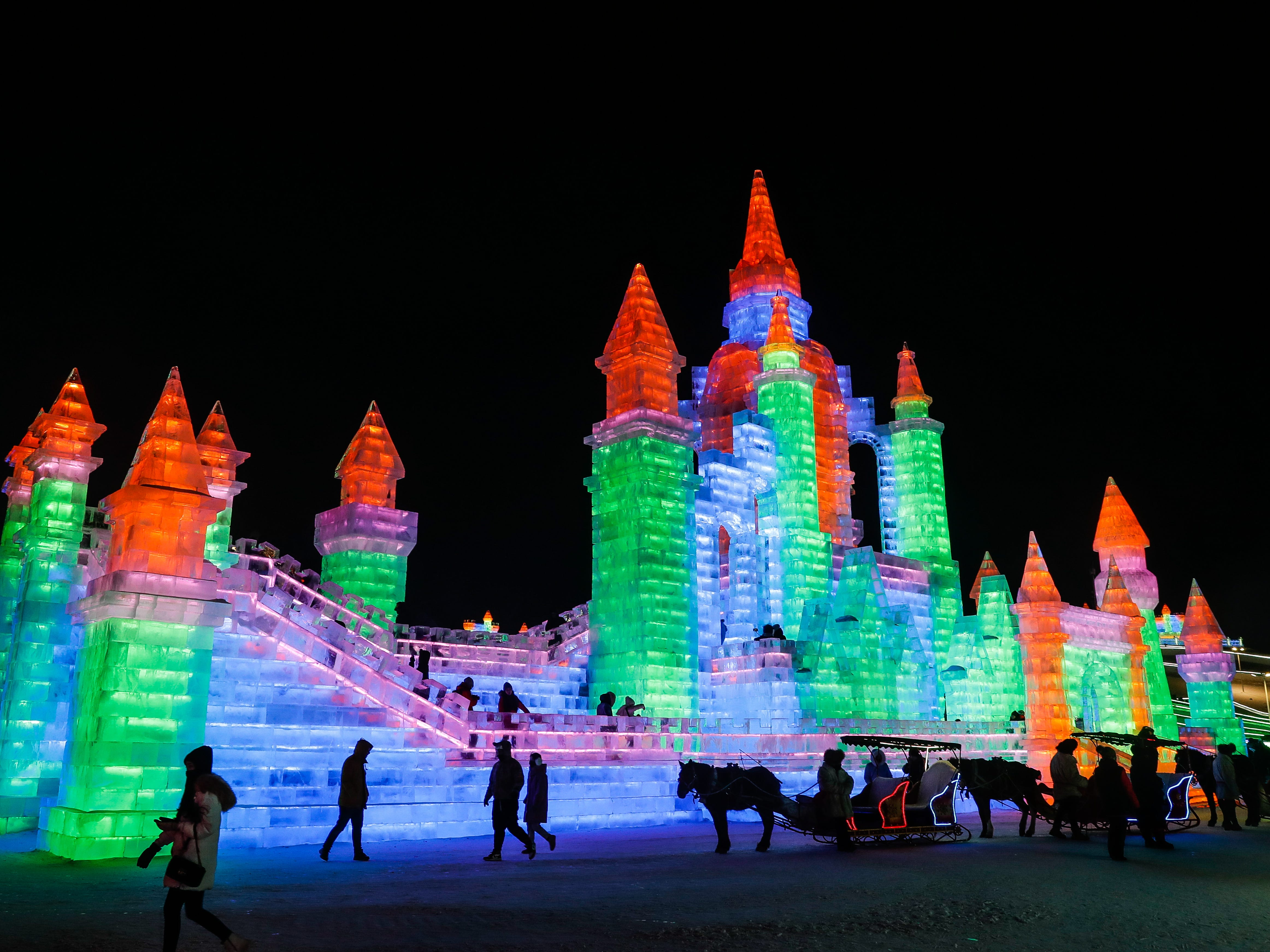 People visit the ice sculptures illuminated by colored lights.