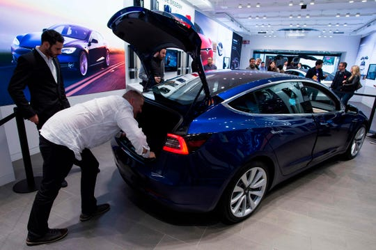 "Two people inspect the rear boot of Tesla's latest car ""Model 3"" during its first exhibition day in Spain, at the Tesla's store in Barcelona Nov. 14, 2018."
