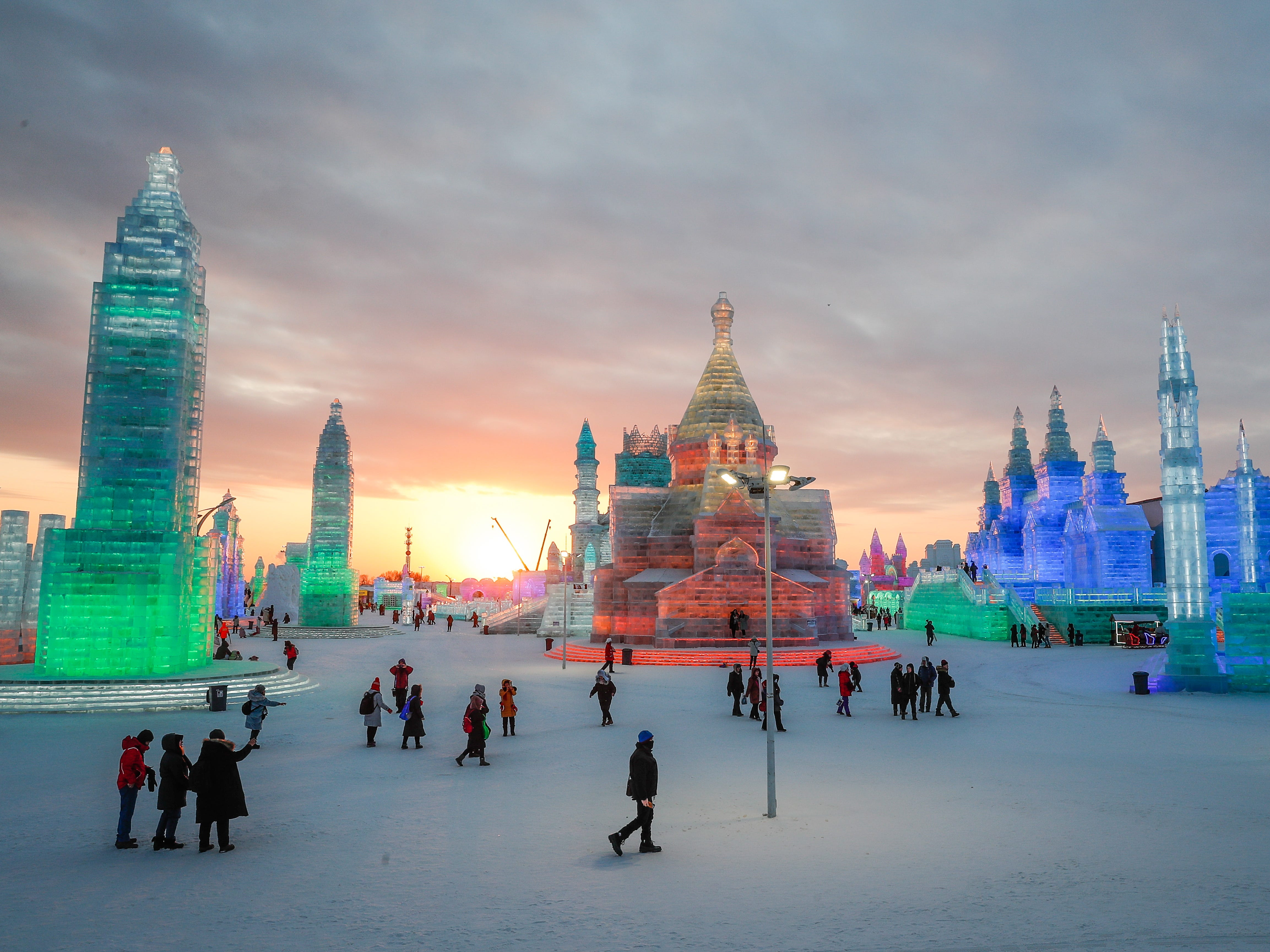 People visit ice sculptures illuminated by colored lights at the Ice and Snow World during the annual Harbin International Ice and Snow Sculpture Festival, in Harbin,   Jan.4,  2019.