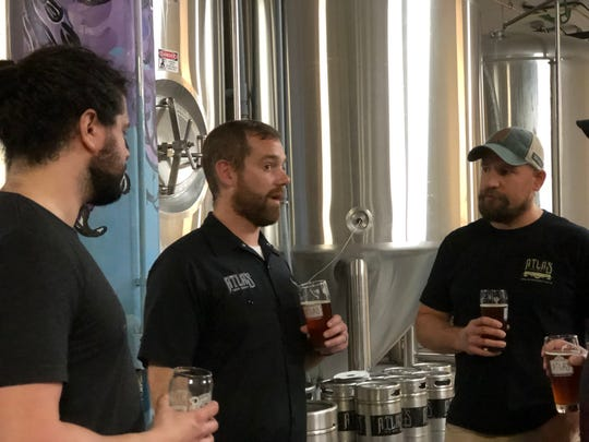 The crew at Atlas Brew Works in Washington, D.C., talk Resilience Butte County Proud IPA. From left, head brewer Daniel Vilarrubi, CEO Justin Cox, and warehouse manager Mark Szymanski, on Dec. 31, 2018.