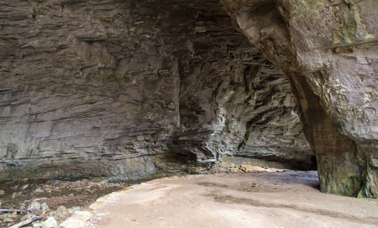 A trail winds through a cavern through which a river flows in Kentucky's Carter Caves State Resort Park.