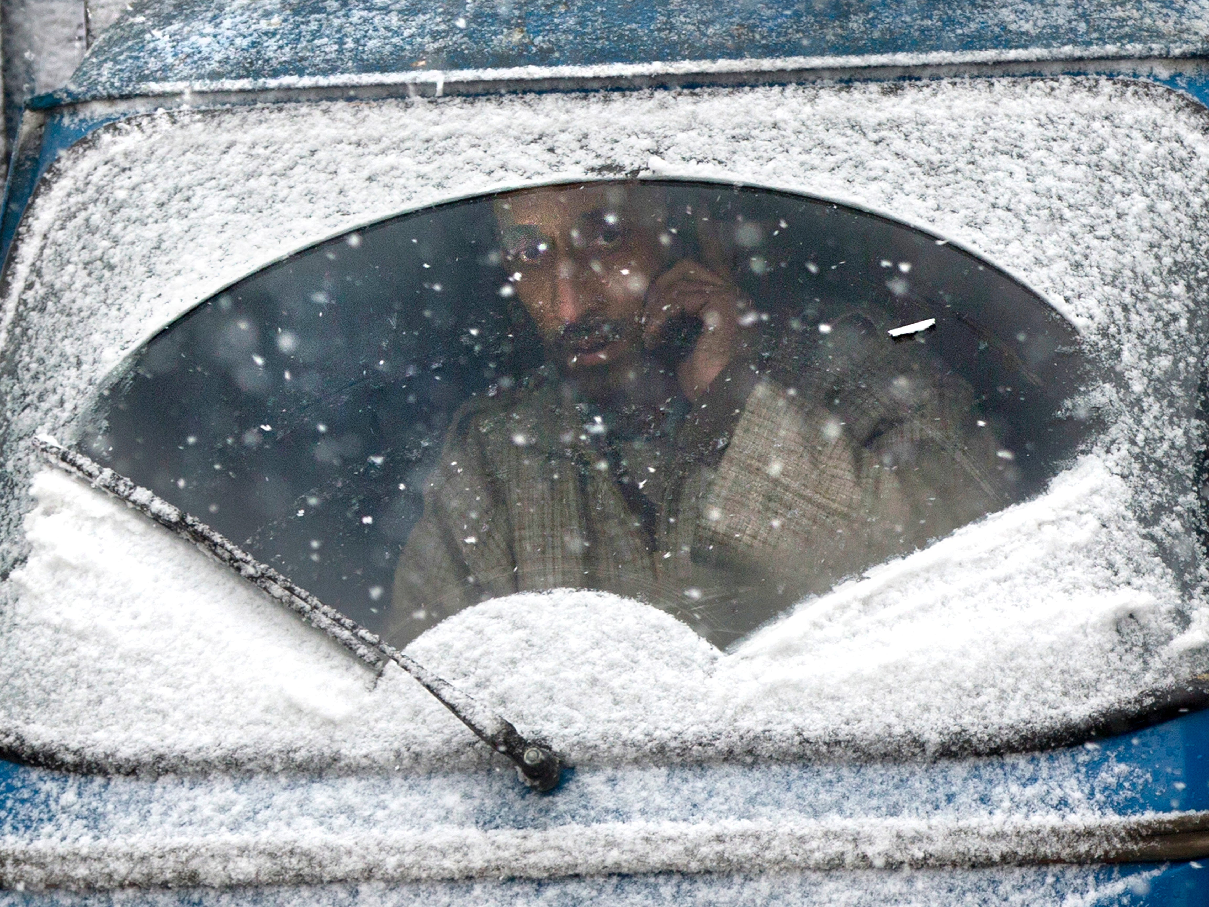 An auto-rickshaw driver looks out from the snow-covered windshield of his vehicle as the fresh snow falls in Srinagar, Indian, Jan. 4, 2019.