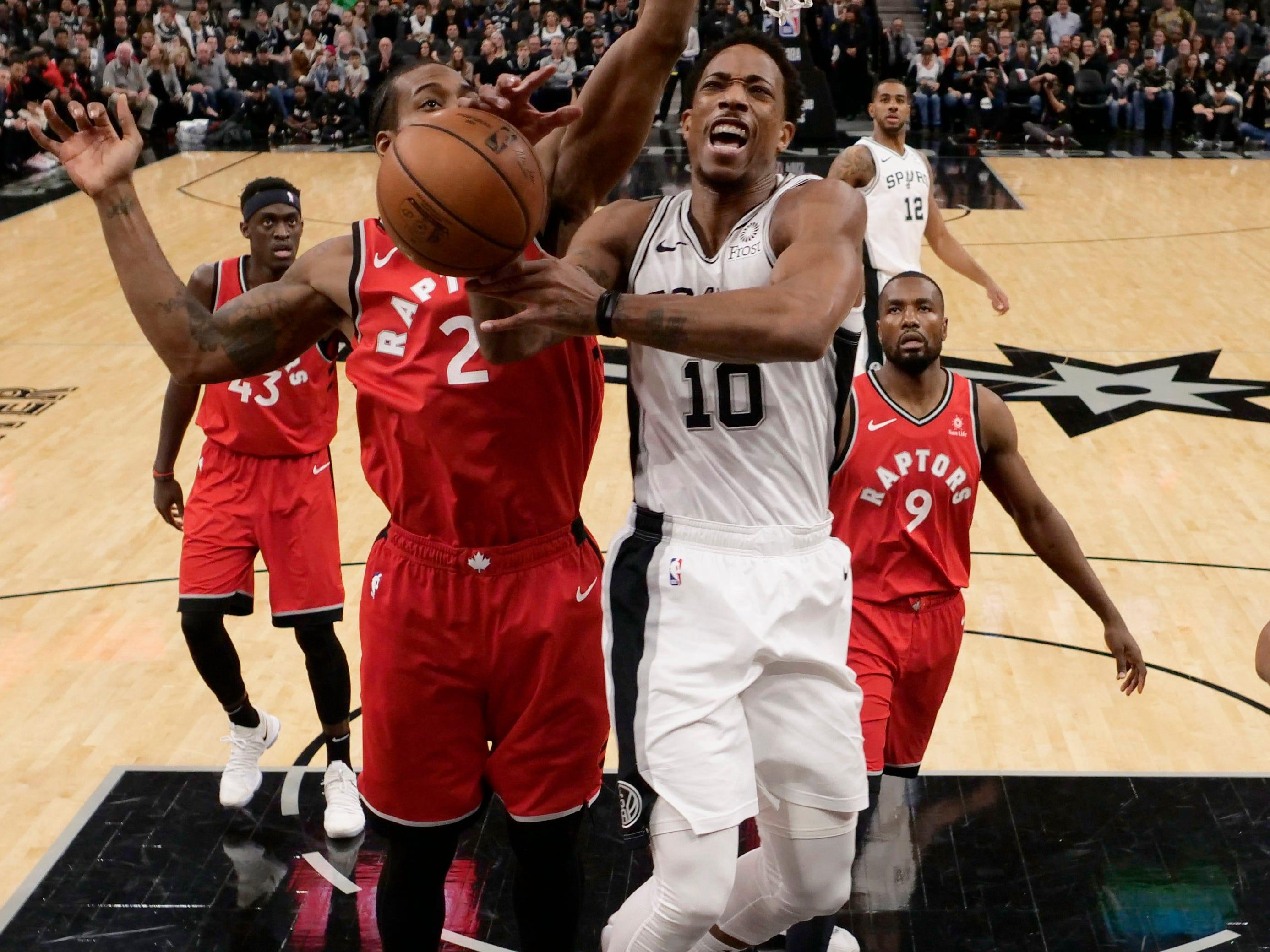 Jan. 3: Raptors defender Kawhi Leonard (2) fouls Spurs guard DeMar DeRozan (10) on a first-half drive to the basket in San Antonio.
