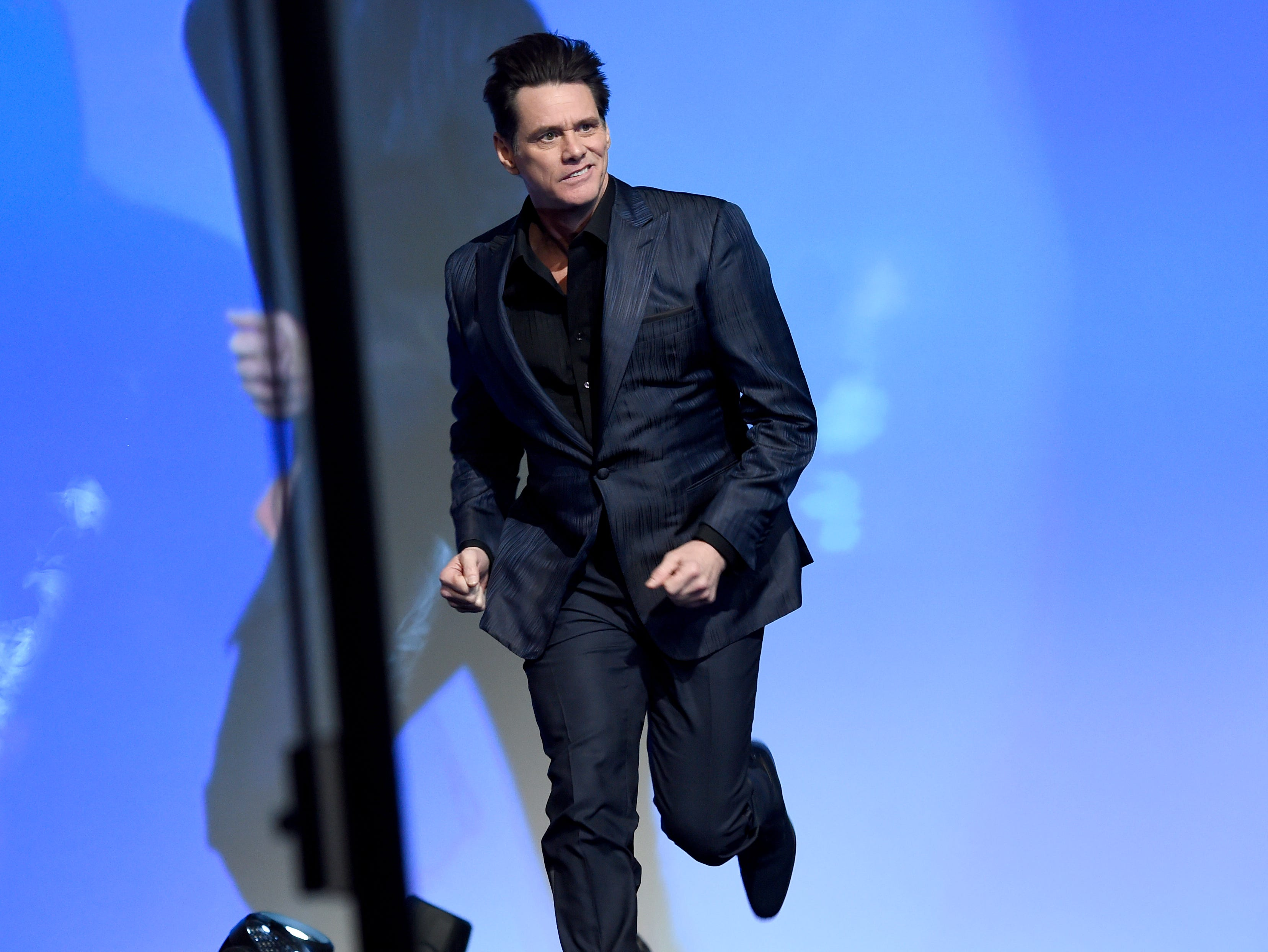 Jim Carrey runs on stage to presents the vanguard award at the 30th annual Palm Springs International Film Festival on Thursday, Jan. 3, 2019, in Palm Springs, Calif. (Photo by Chris Pizzello/Invision/AP) ORG XMIT: CADC255