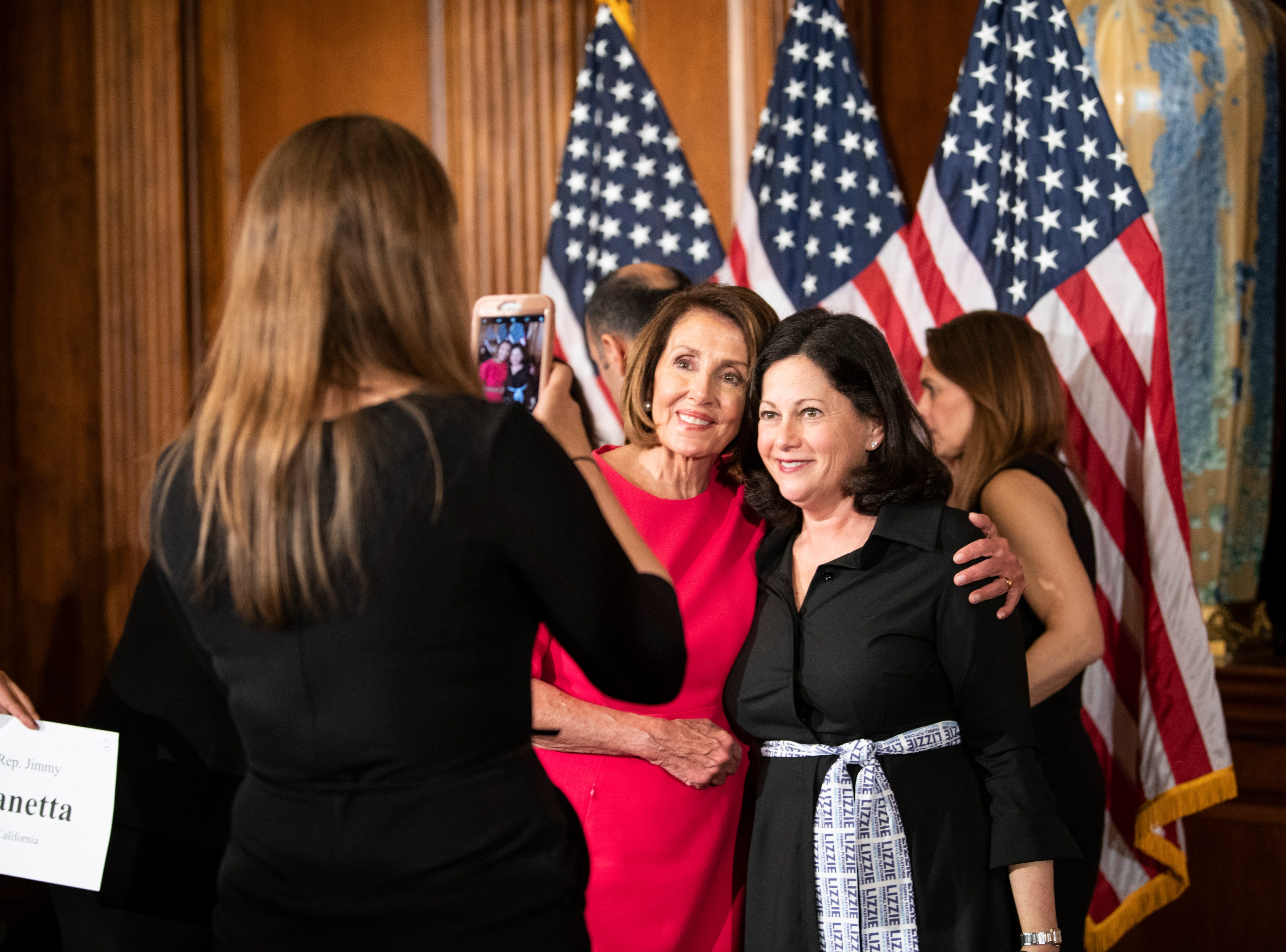 House Speaker Nancy Pelosi poses with a member of Representative Lizzie Fletcher's (D, TX) family during the swearing in ceremony.