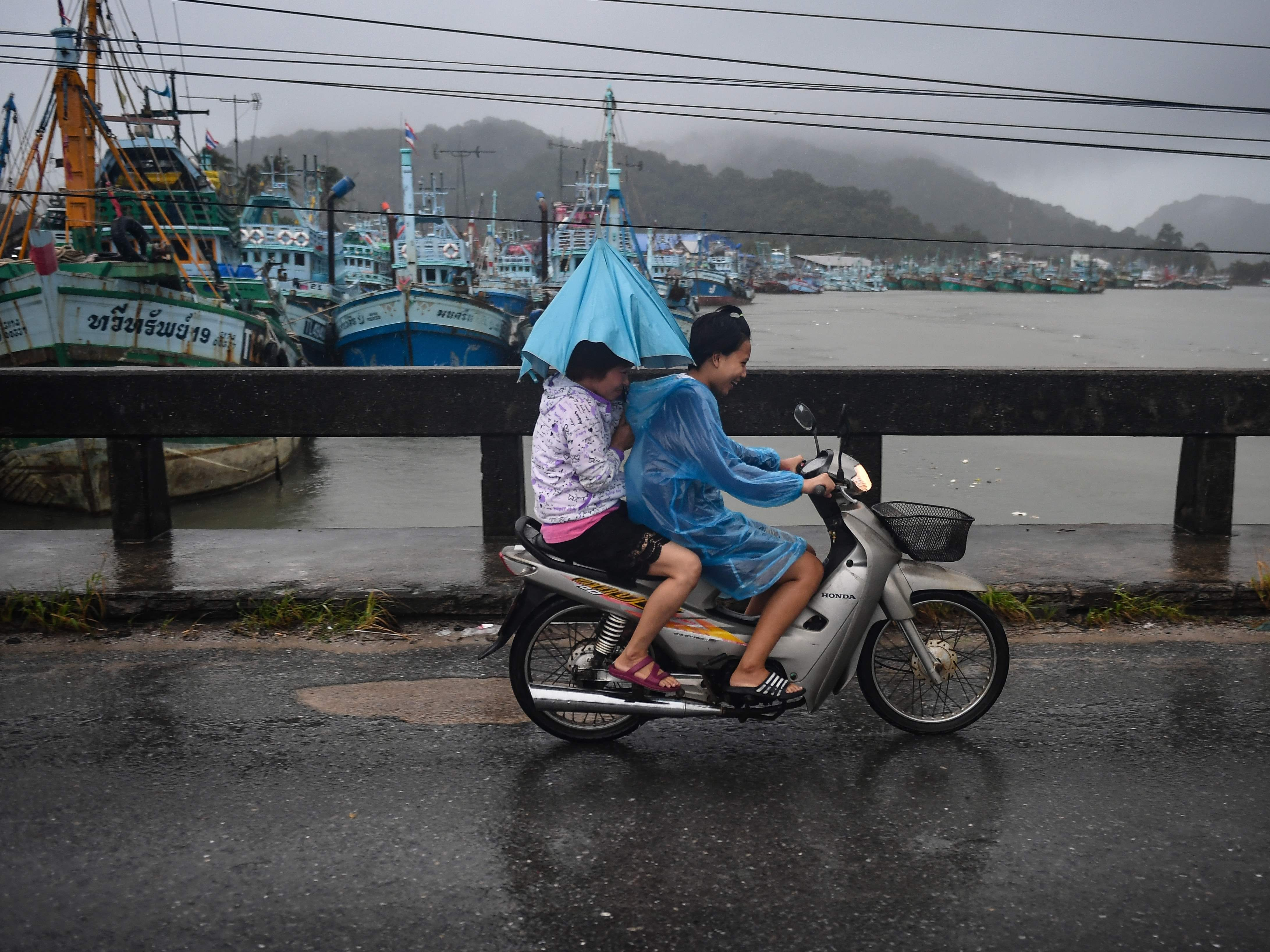 Two girls drive through heavy rain due to tropical storm Pabuk in the southern Thai province of Nakhon Si Thammarat on January 4, 2019. - Tens of thousands of tourists have fled some of Thailand's most popular islands and resort areas as Tropical Storm Pabuk closes in and threatens to batter the southern part of the kingdom with heavy rains, winds and seven-metre (22-foot) waves. (Photo by Lillian SUWANRUMPHA / AFP)LILLIAN SUWANRUMPHA/AFP/Getty Images ORIG FILE ID: AFP_1BZ0N3