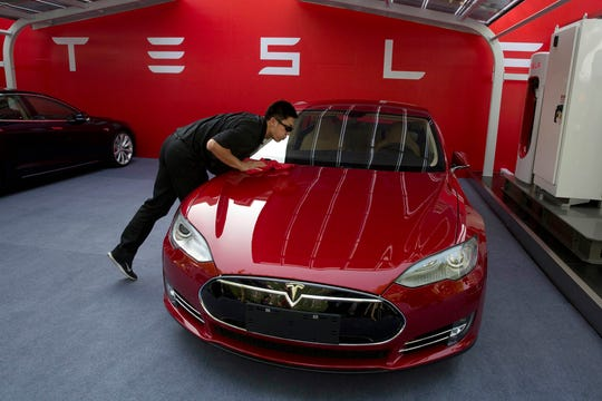 A worker cleans a Tesla Model S sedan before an event to deliver the first set of cars to customers in Beijing, April 22, 2014.