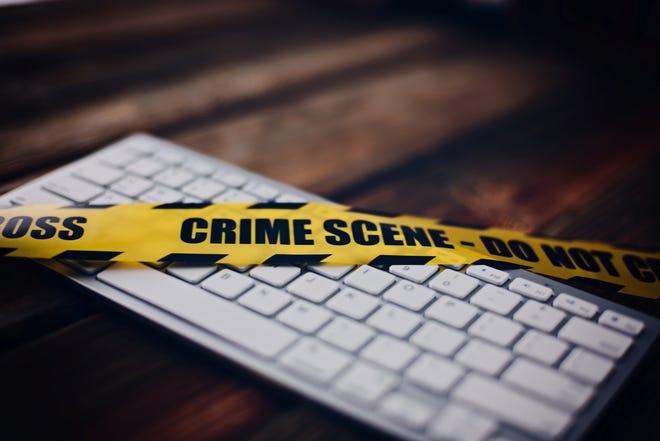 Yellow crime scene tape on computer keyboard. Computer crime concept.Yellow crime scene tape on computer keyboard. Computer crime concept.
