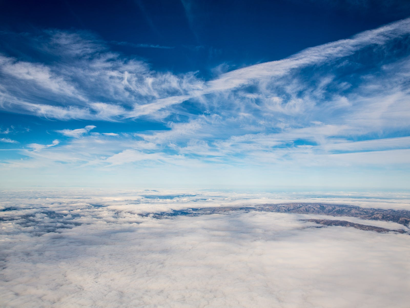 Wispy clouds fill the skies over a foggy Bay Area in December 2018.