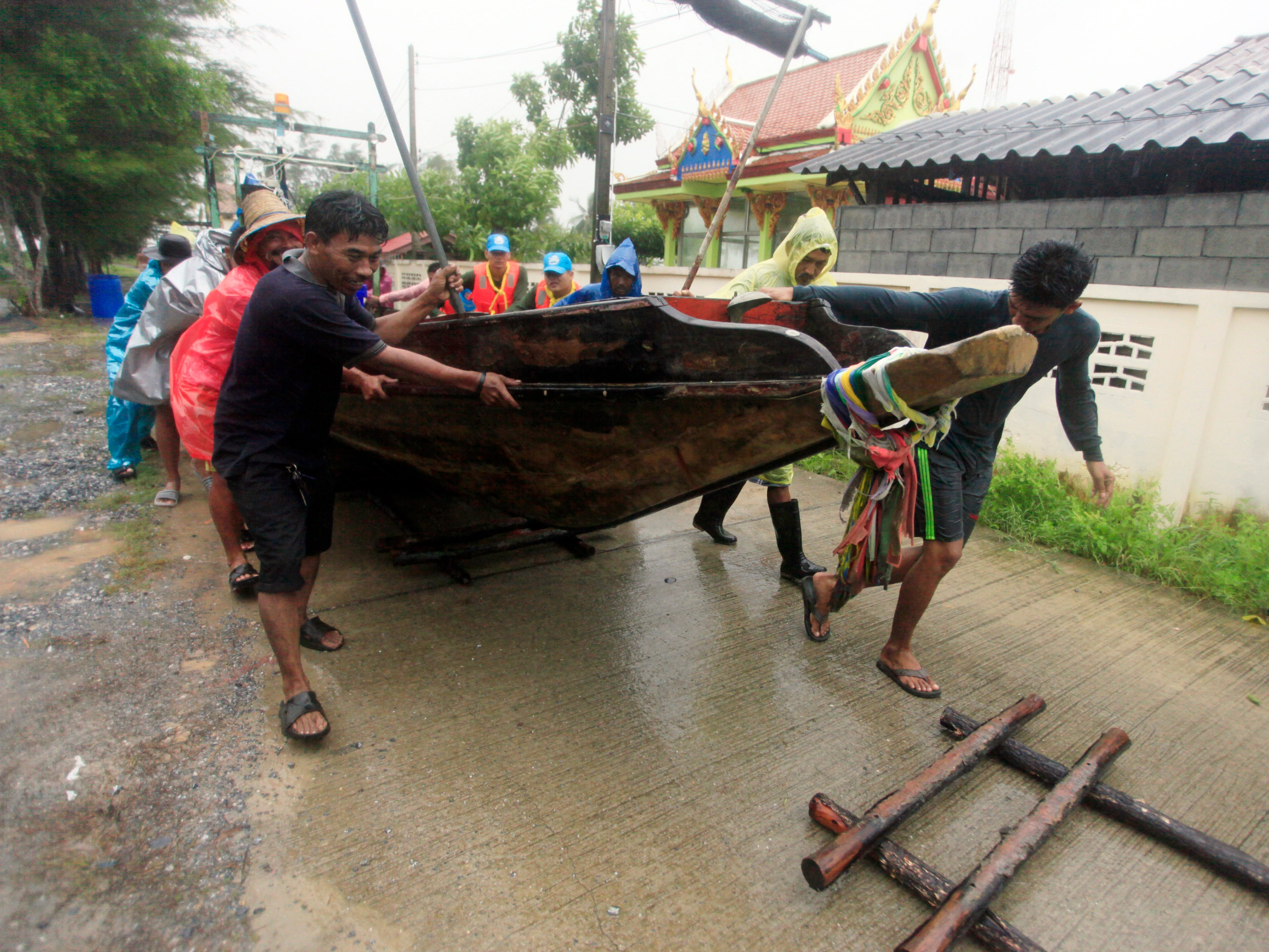 Local fishermen move a boat ashore in preparation for the approaching Tropical Storm Pabuk, Friday, Jan. 4, 2019, in Pak Phanang, in the southern province of Nakhon Si Thammarat, southern Thailand. Rain, winds and surging seawater are striking southern Thailand as a strengthening tropical storm nears coastal villages and popular tourist resorts. (AP Photo/Sumeth Panpetch) ORG XMIT: BKWS101