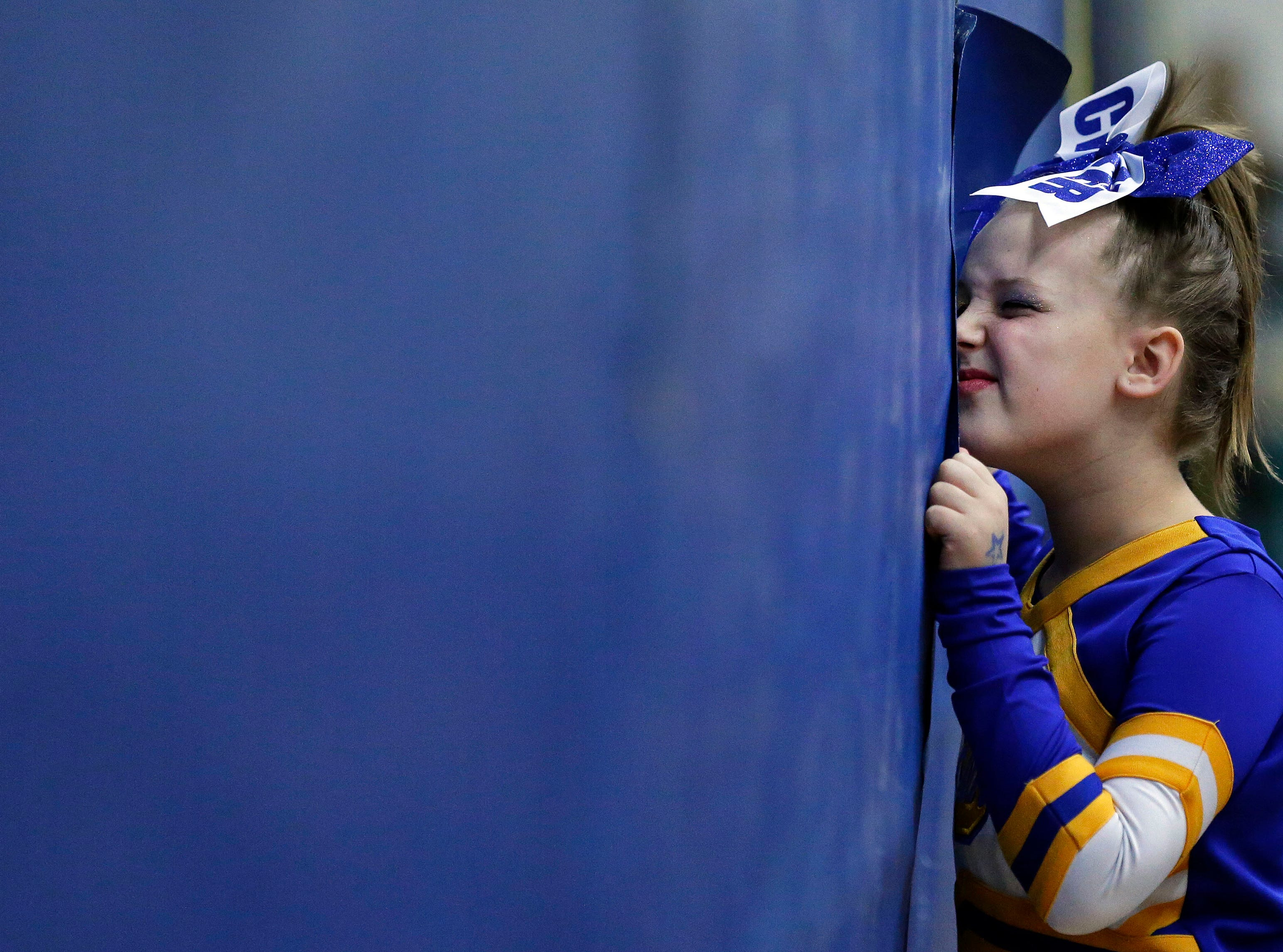 An Oconto Falls team member watches the competition as her team waits to warm-up as the Lightning Bolt Explosion Cheer and Dance competition takes place Saturday, January 5, 2019, at Appleton North High School in Appleton, Wis.