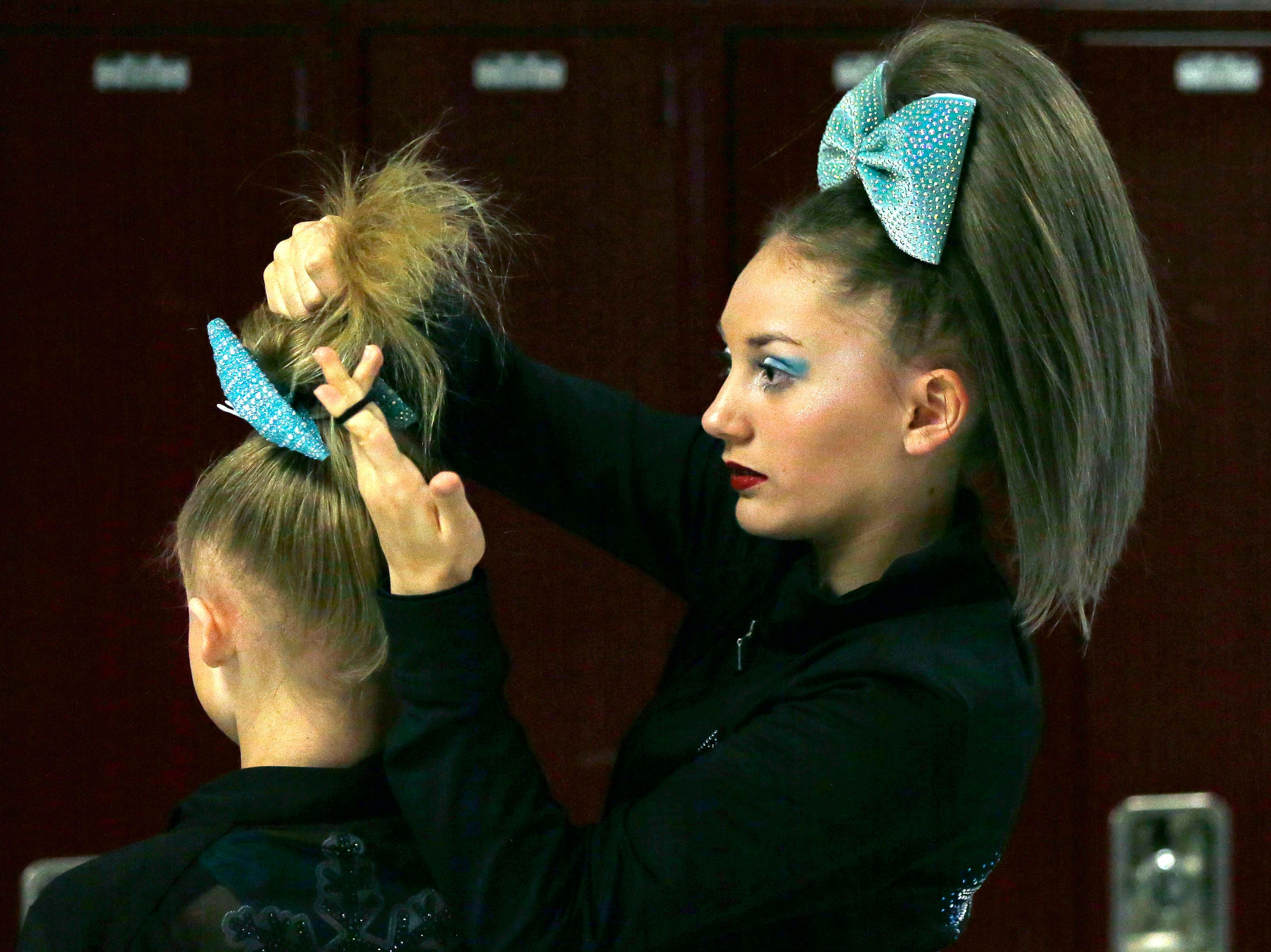 Vanessa Korth, left, of WIDC gets help with her hair from Ava Knudson as the Lightning Bolt Explosion Cheer and Dance competition takes place Saturday, January 5, 2019, at Appleton North High School in Appleton, Wis.