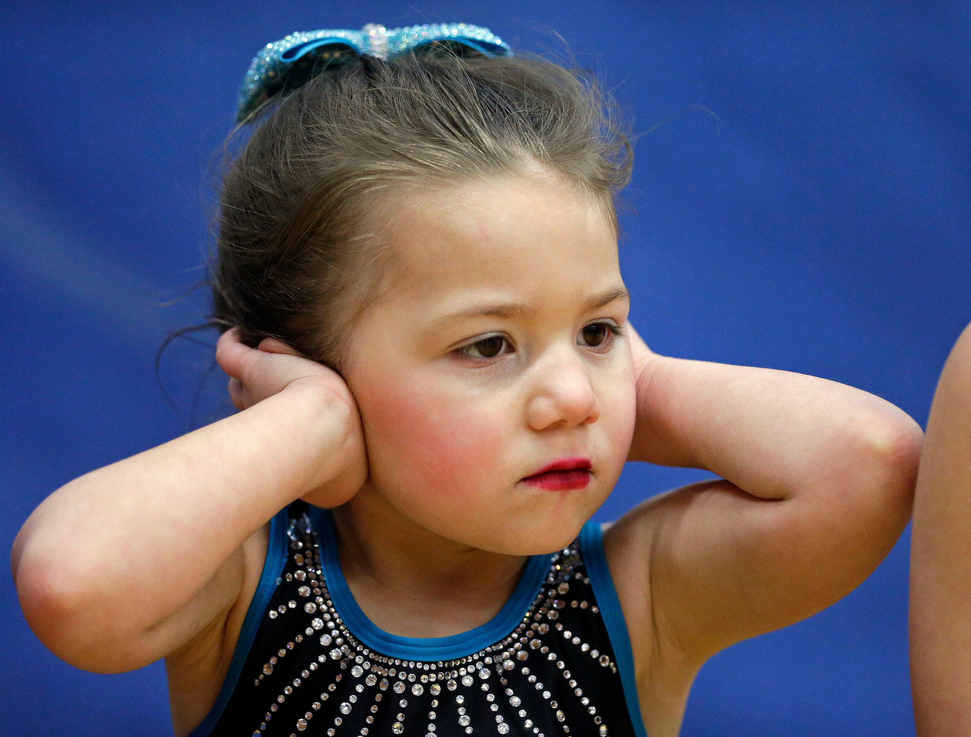 A member of the WIDC Penguins covers her ears as she waits to compete in the Lightning Bolt Explosion Cheer and Dance competition Saturday, January 5, 2019, at Appleton North High School in Appleton, Wis.