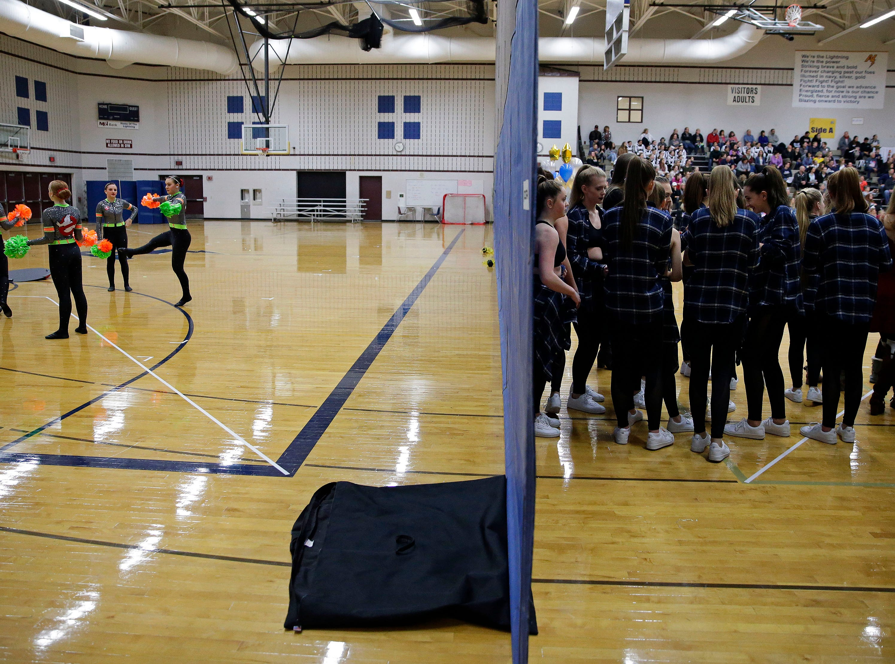 Teams warm-up on the left and are ready to take the floor on the right as the Lightning Bolt Explosion Cheer and Dance competition takes place Saturday, January 5, 2019, at Appleton North High School in Appleton, Wis.