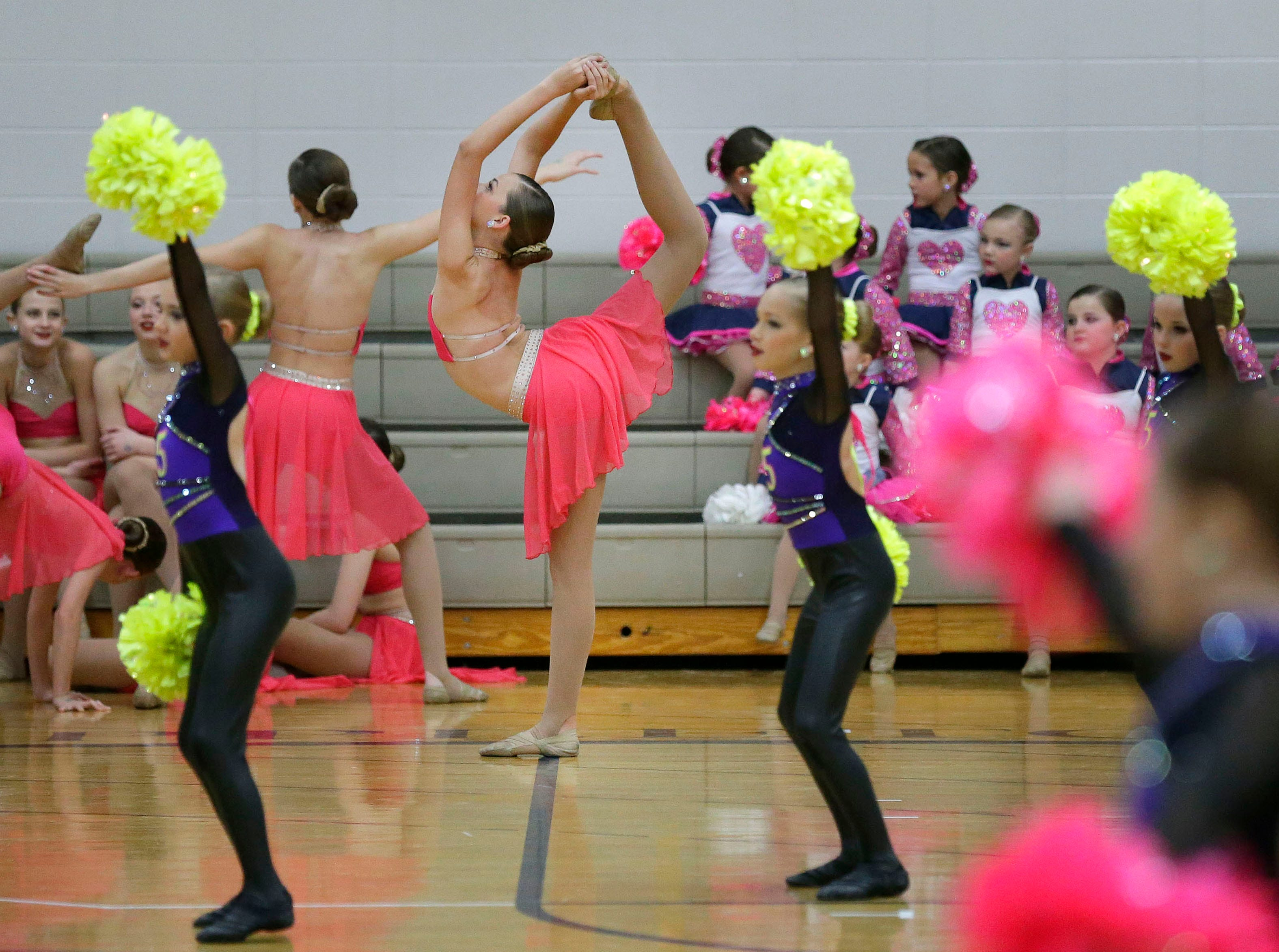 Chloe Dulski with the Energizers Dance Team gets ready while the Energizers Mini Pom Team practices their routine in the foreground as the Lightning Bolt Explosion Cheer and Dance competition takes place Saturday, January 5, 2019, at Appleton North High School in Appleton, Wis.