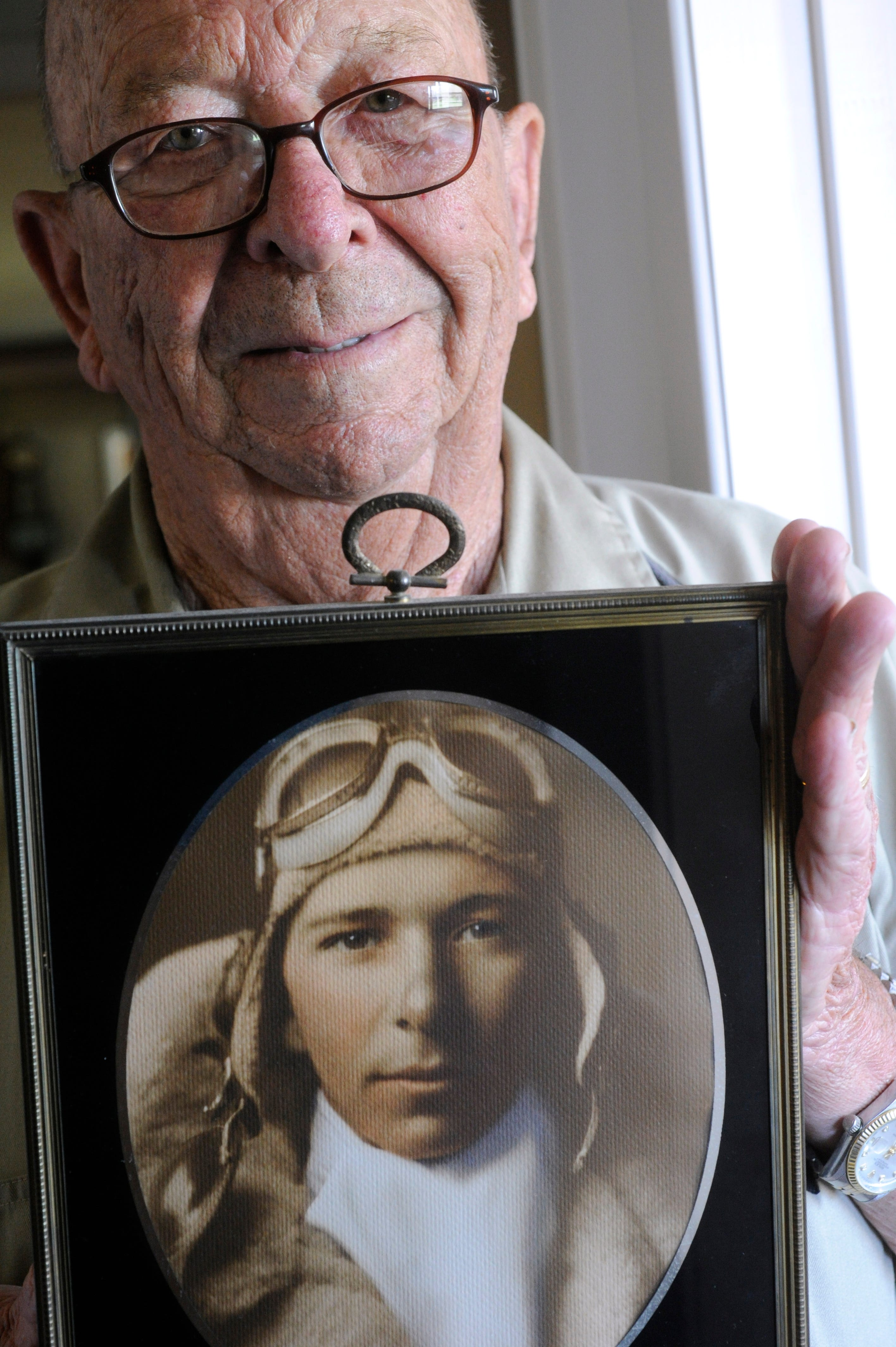 Wes Hays, former mayor of Winters and World War II combat pilot, at his home in Novice on May 26, 2011. Hays holds a portrait of himself taken at the U.S. Naval Schools of Photography in1 943 before eventually shipping out to the Pacific theater.