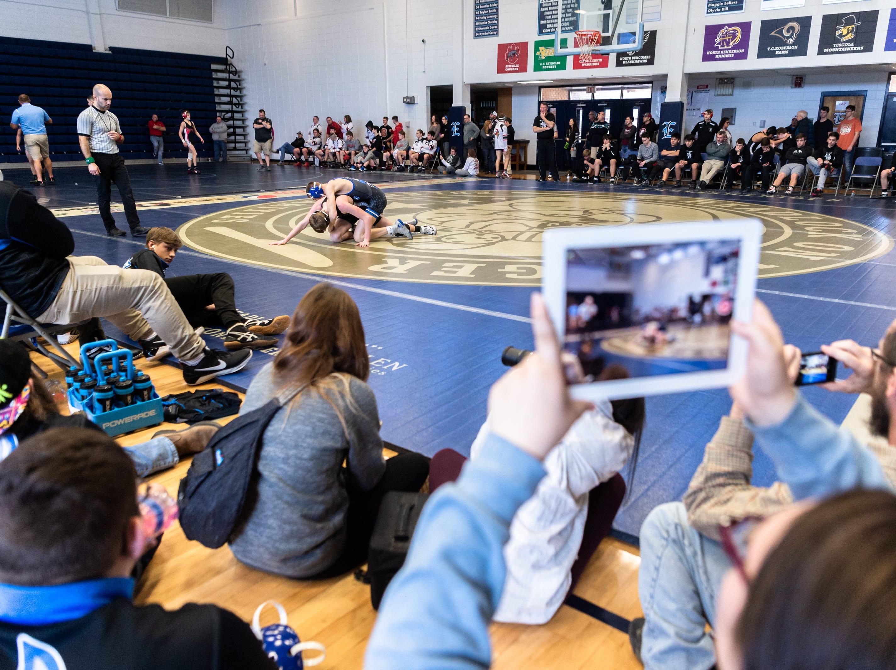 Spectators watch a match during Eblen Charities' Headlock on Hunger wrestling tournament at Enka High School Jan. 5, 2018.