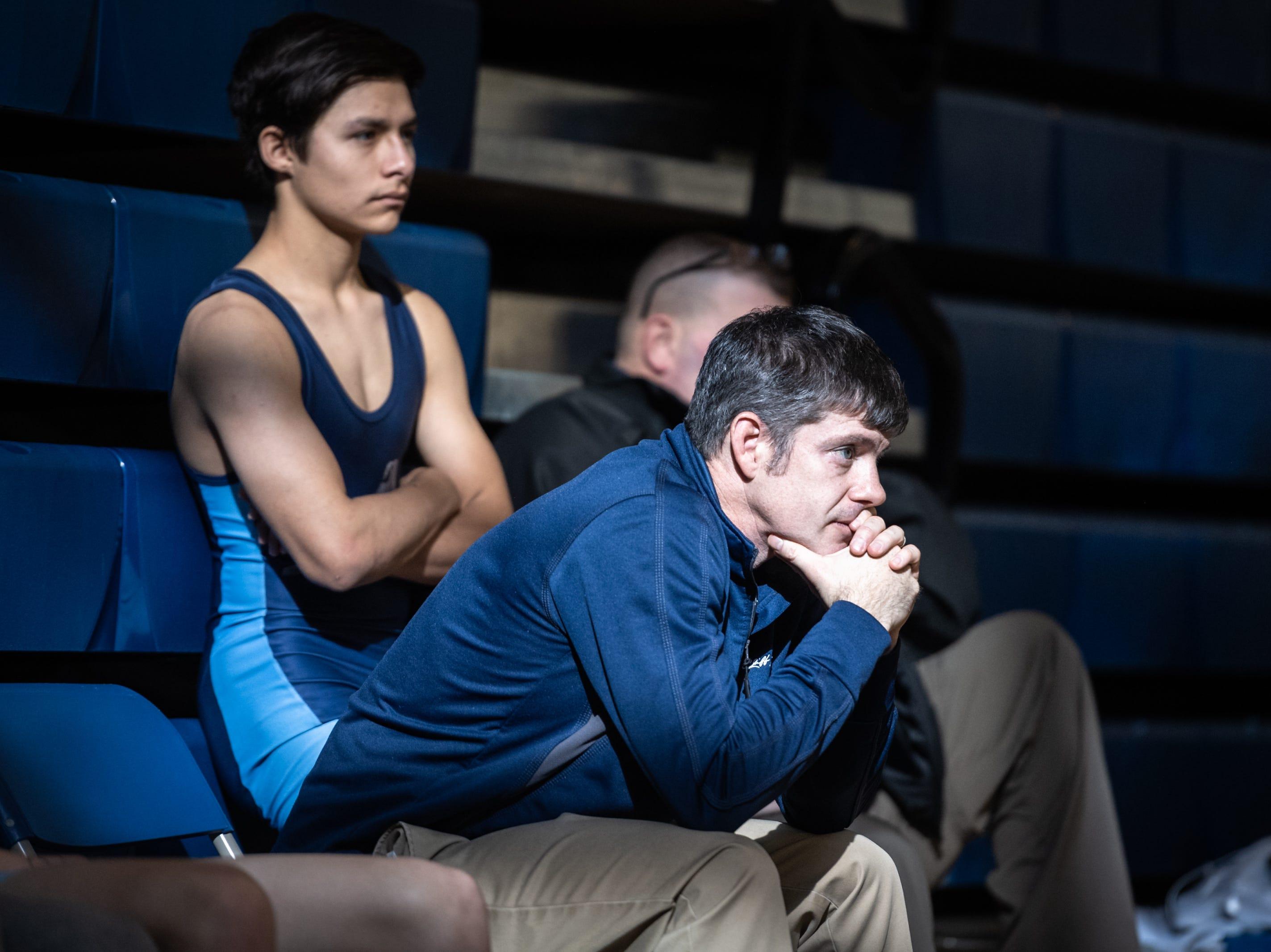 Enka High School wrestling coach, Mark Harris watches a match during Eblen Charities' Headlock on Hunger wrestling tournament at Enka High School Jan. 5, 2018.