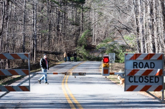 Visitors to the Blue Ridge Parkway walk along a section of the parkway beyond a gate where there is a fallen tree just north of the Folk Art Center Jan. 5, 2019. Much of the Parkway has been closed due to the government shut down and maintenance such as clearing debris is not possible.