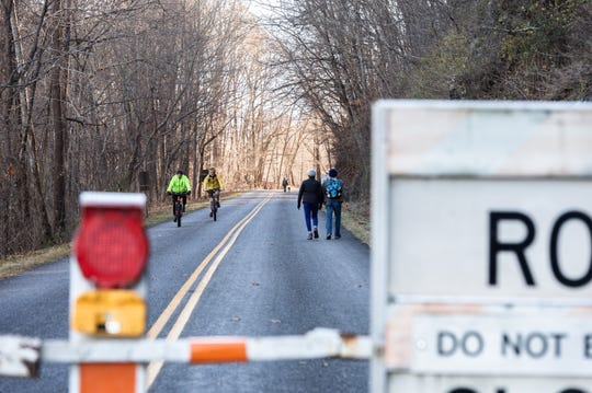 Visitors to the Blue Ridge Parkway walk along a section of the parkway beyond a closed gate just south of the North Carolina Arboretum Jan. 5, 2019. Much of the Parkway has been closed due to the government shut down.