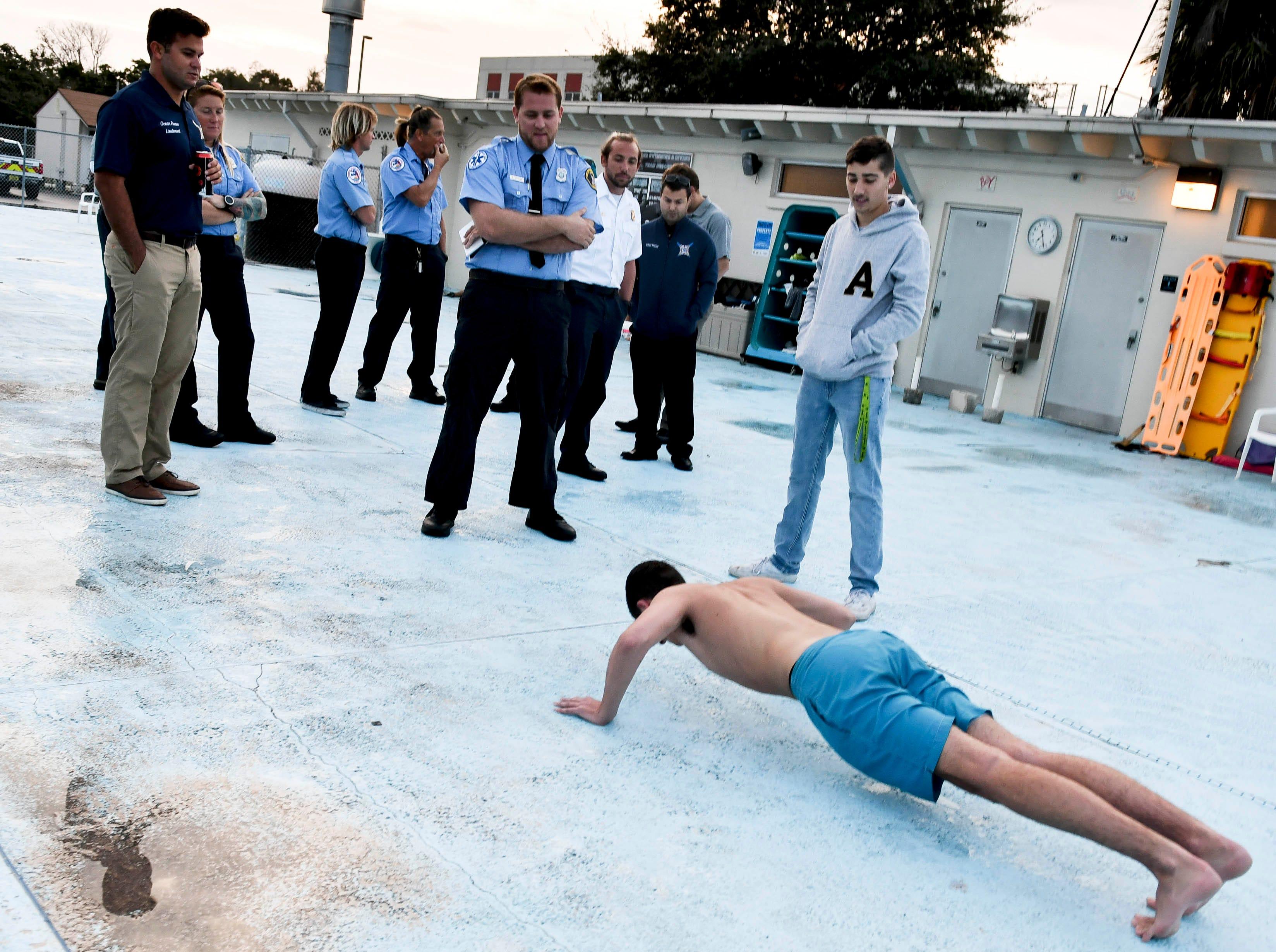 Lifeguards watch as Nicholas Forney does pushups as part of his tryout for a lifeguard position early Saturday morning.