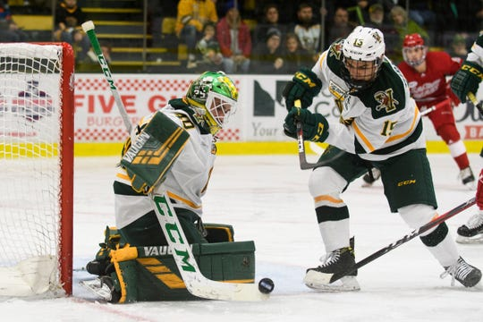 Vermont goalie Stefanos Lekkas (40) makes a save as Vermont defenseman Corey Moriarty (15) looks on during the men's hockey game between the Sacred Heart Pioneers and the Vermont Catamounts at Gutterson Field House on Friday night January 4, 2019 in Burlington.