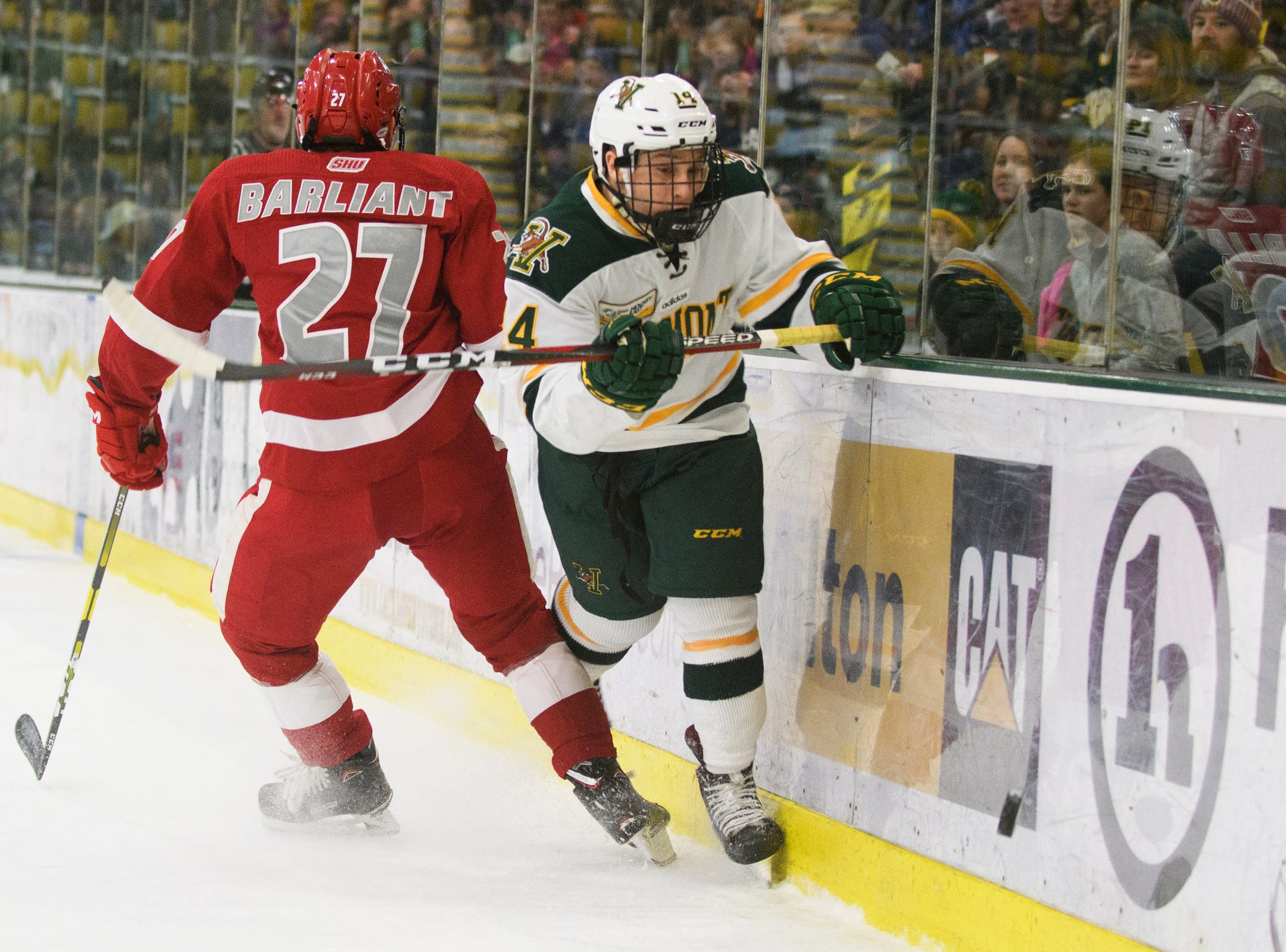 Vermont forward Ace Cowans (14) battles for the puck along the boards with Sacred Heart's Jackson Barliant (27) during the men's hockey game between the Sacred Heart Pioneers and the Vermont Catamounts at Gutterson Field House on Friday night January 4, 2019 in Burlington.