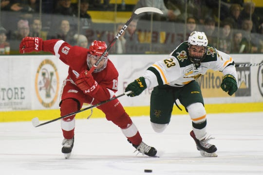 Vermont forward Max Kaufman (23) and Sacred Heart's Jordan Kaplan (13) chase down the puck during the men's hockey game between the Sacred Heart Pioneers and the Vermont Catamounts at Gutterson Field House on Friday night January 4, 2019 in Burlington.
