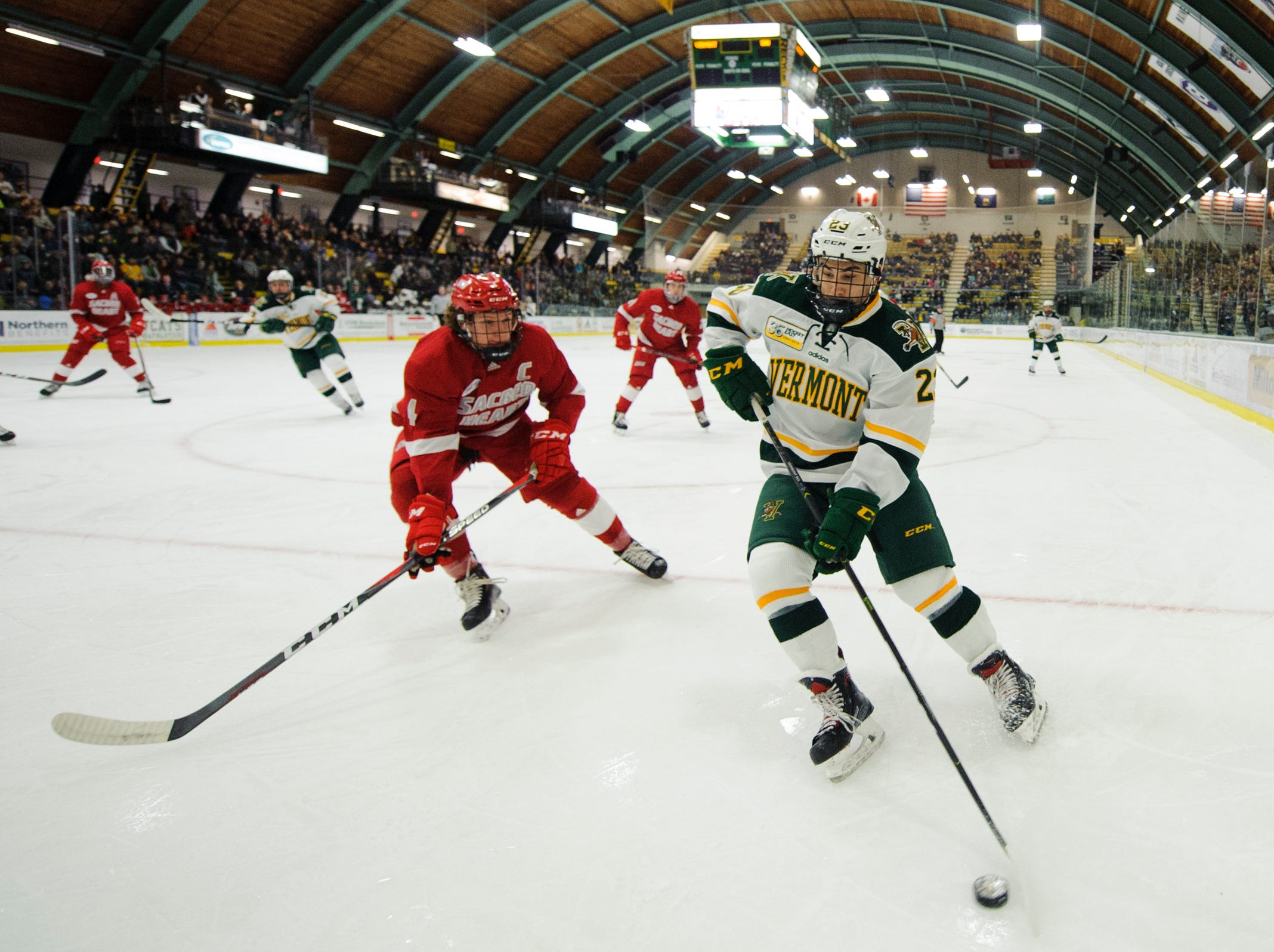 Vermont forward Max Kaufman (23) plays the puck in the corner during the men's hockey game between the Sacred Heart Pioneers and the Vermont Catamounts at Gutterson Field House on Friday night January 4, 2019 in Burlington.