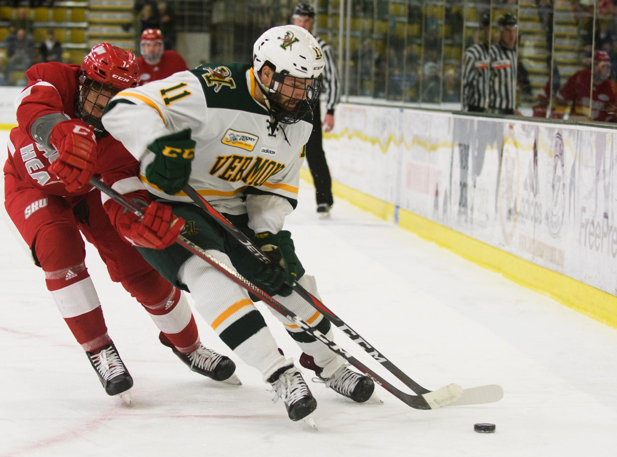 Vermont forward Conor O'Neil (11) battles for the puck with Sacred Heart's Drennen Atherton (1) during the men's hockey game between the Sacred Heart Pioneers and the Vermont Catamounts at Gutterson Field House on Friday night January 4, 2019 in Burlington.