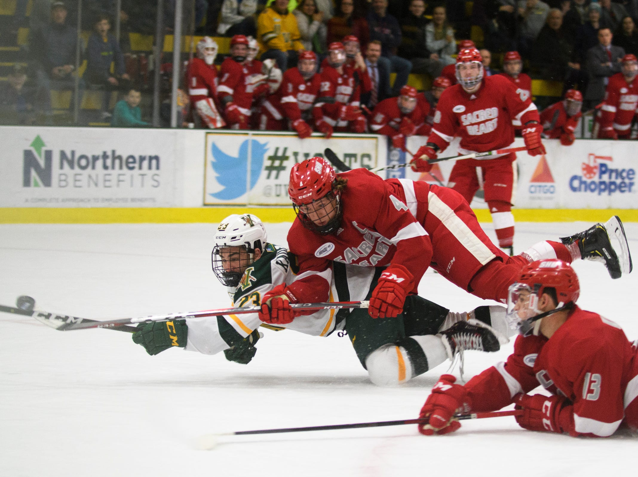 Vermont forward Max Kaufman (23) battles for the puck with Sacred Heart's Liam Clare (4) and Jordan Kaplan (13) during the men's hockey game between the Sacred Heart Pioneers and the Vermont Catamounts at Gutterson Field House on Friday night January 4, 2019 in Burlington.