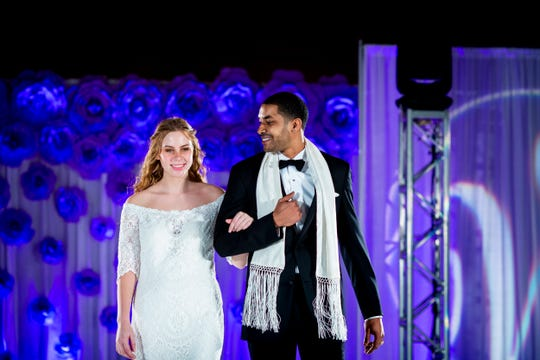 Two models walk down the runway in the latest wedding dress and suit styles for the fashion show at the Wendy's Bridal Show at the Duke Energy Convention Center Saturday, January 5, 2019 in Downtown Cincinnati.