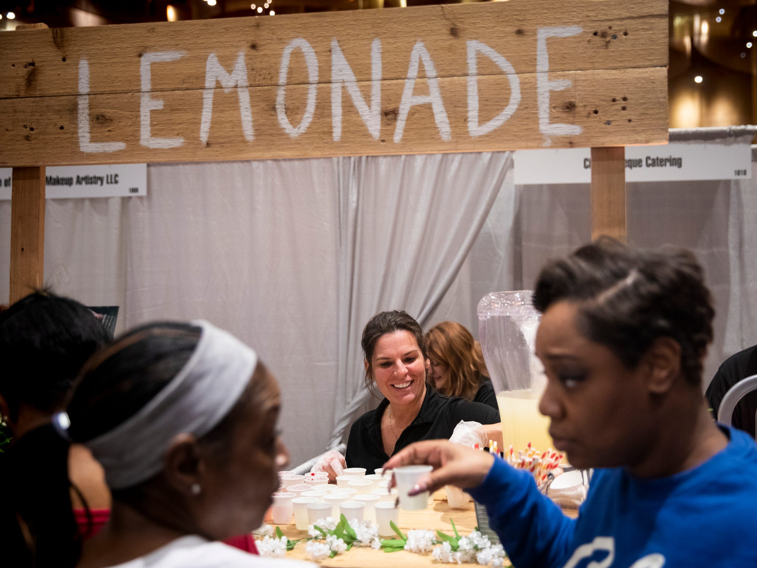 Hillary Fishel serves refreshing drinks from a lemonade stand at City Barbecue's booth at the Wendy's Bridal Show at the Duke Energy Convention Center Saturday, January 5, 2019 in Downtown Cincinnati.