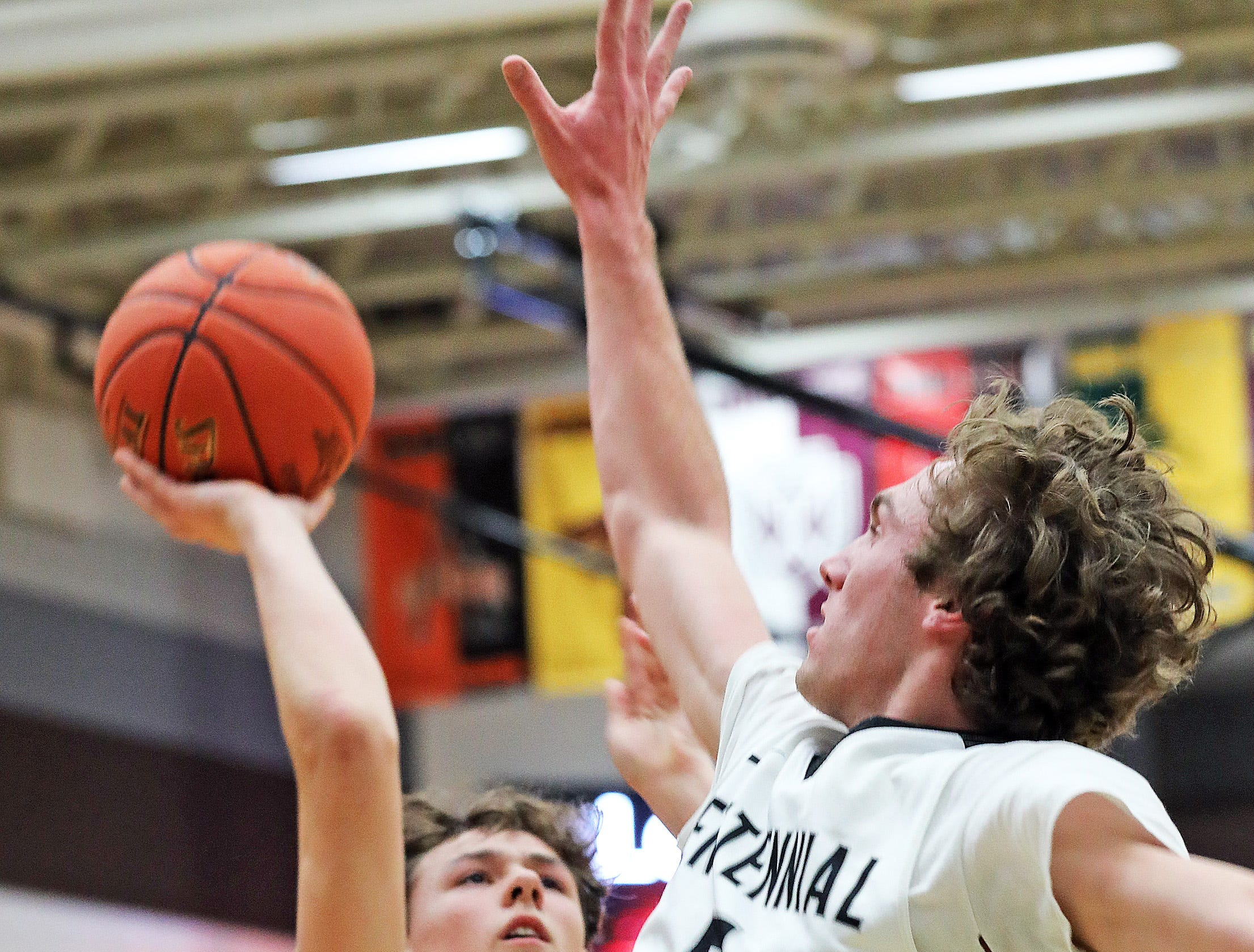 Ankeny Centennial junior Preston Kelling flies in for the block on Johnston sophomore Reid Grant as the Johnston Dragons compete against the Ankeny Centennial Jaguars in high school boys basketball on Friday, Jan. 4, 2019 at Ankeny Centennial High School.