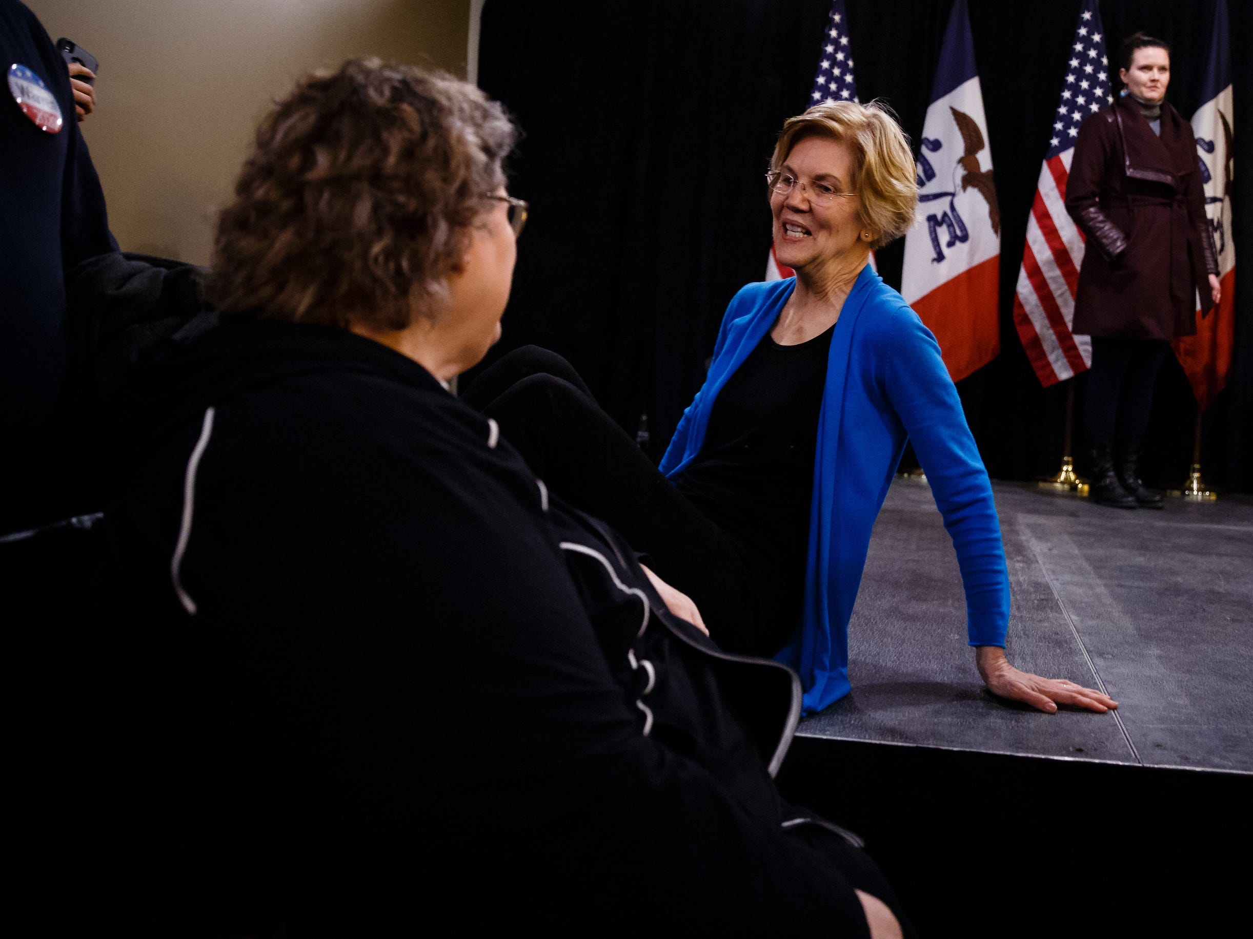 Sen. Elizabeth Warren crouches down to talk to a woman in a wheelchair during an event on her first trip through Iowa as a possible 2020 presidential candidate on Friday, Jan. 4, 2019, in Council Bluffs.