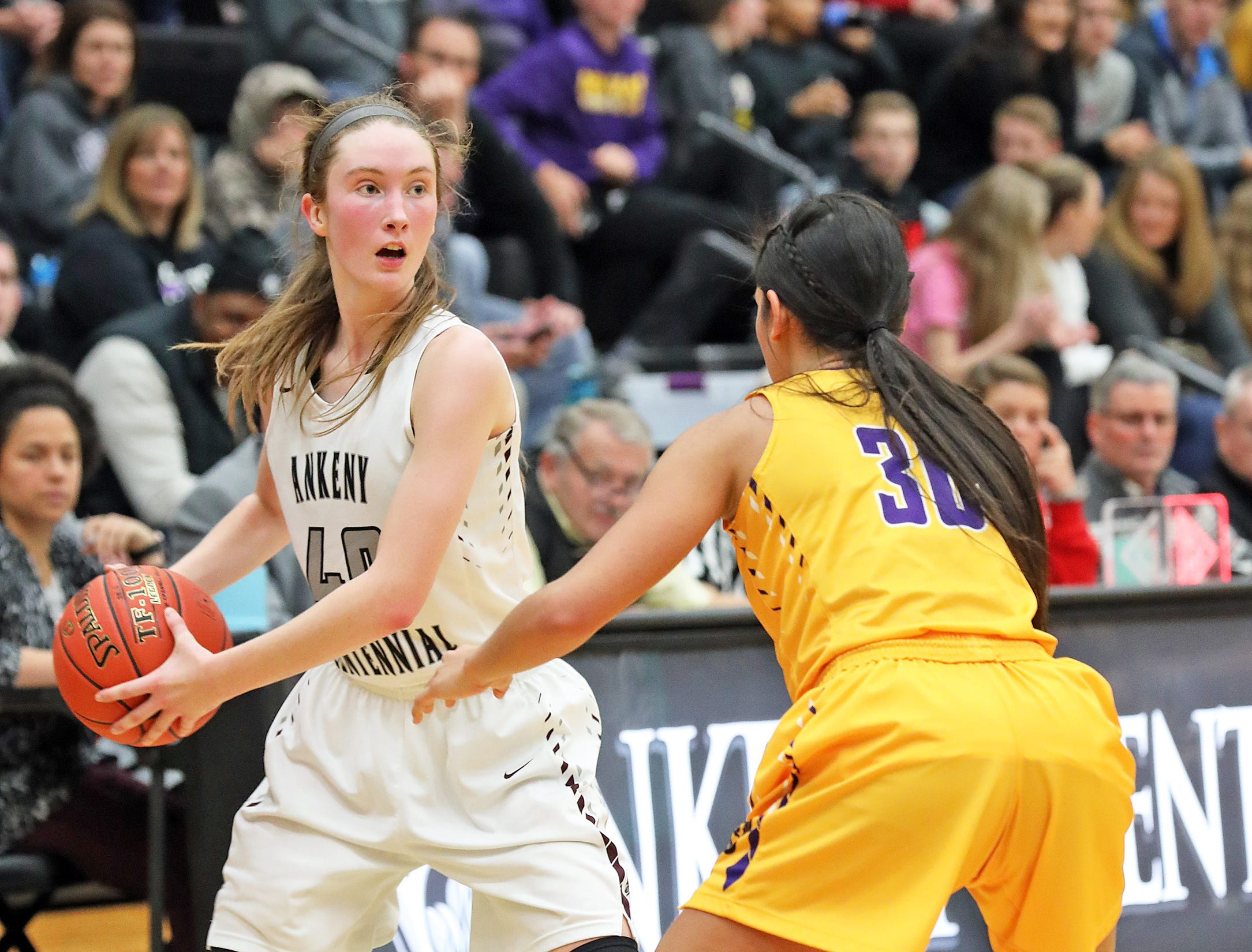 Ankeny Centennial junior Meg Burns looks to pass around Johnston junior Kendall Nead as the Johnston Dragons compete against the Ankeny Centennial Jaguars in high school girls basketball on Friday, Jan. 4, 2019 at Ankeny Centennial High School.