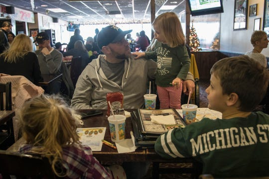 Dan Vavrick talks to his daughter Caroline, 2, as his older daughter Evelyn, 4, and son Bennett, 7, enjoy coloring at the table at Mr. B's Food & Spirits in Rochester, Saturday, Jan. 5, 2019.