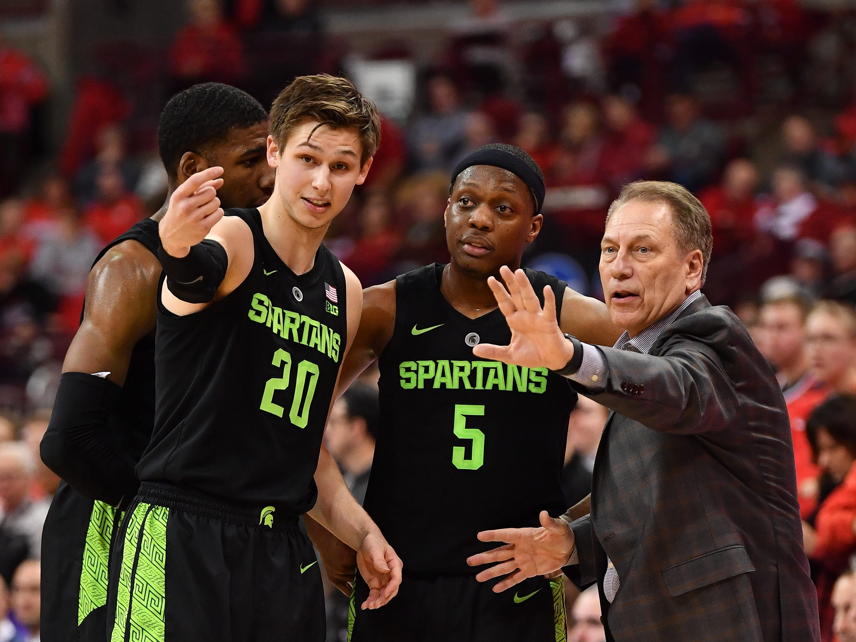 Michigan State's Matt McQuaid (20) and Cassius Winston (5) talk with coach Tom Izzo in the second half against Ohio State on Jan. 5, 2019 at Value City Arena in Columbus, Ohio.