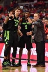 Matt McQuaid (20) and Cassius Winston (5) talk with coach Tom Izzo in the second half against Ohio State on Saturday.