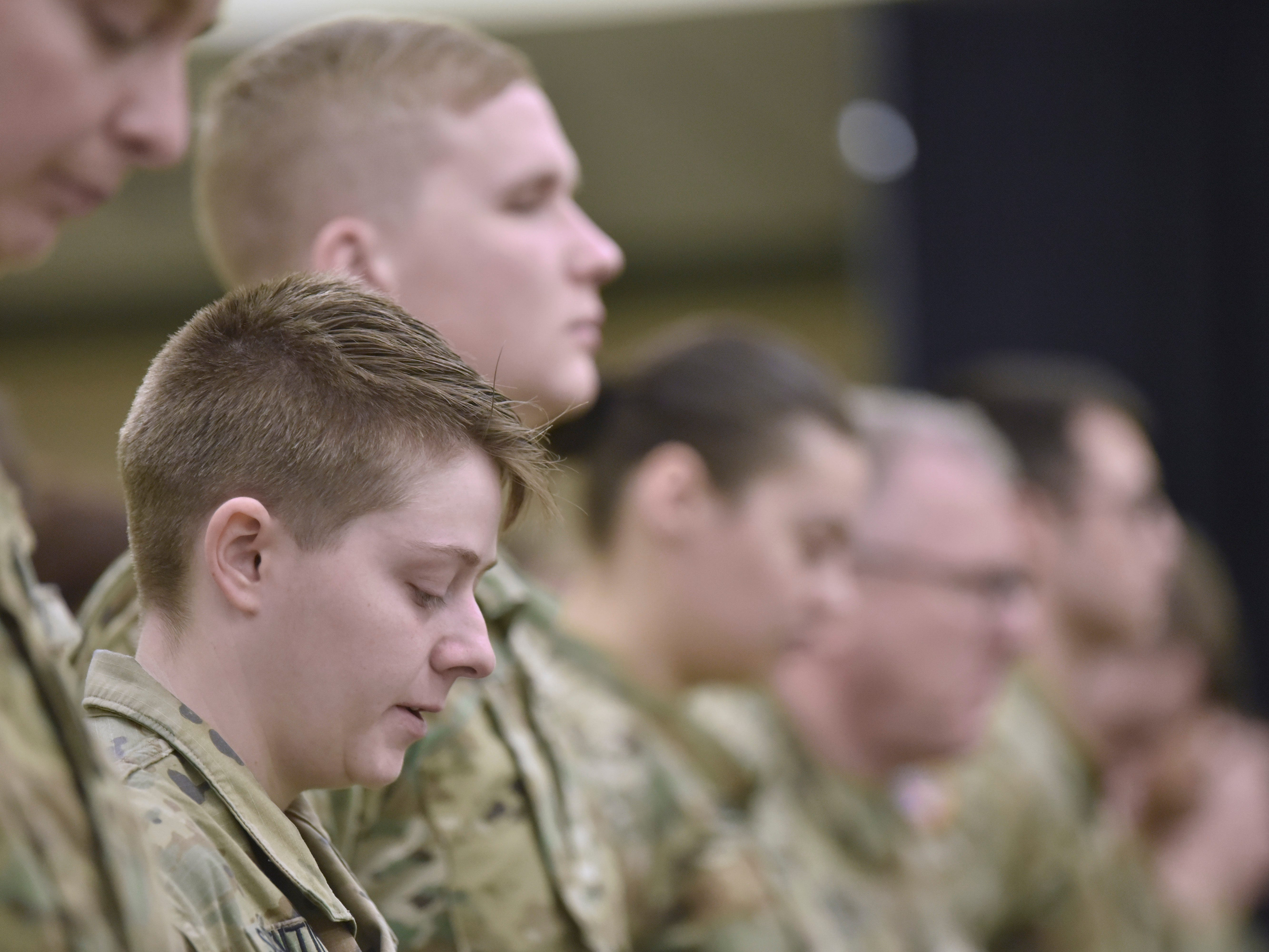 Sgt. Jessica Sorrentino and other Michigan Army National Guard Unit members pray during the benediction.