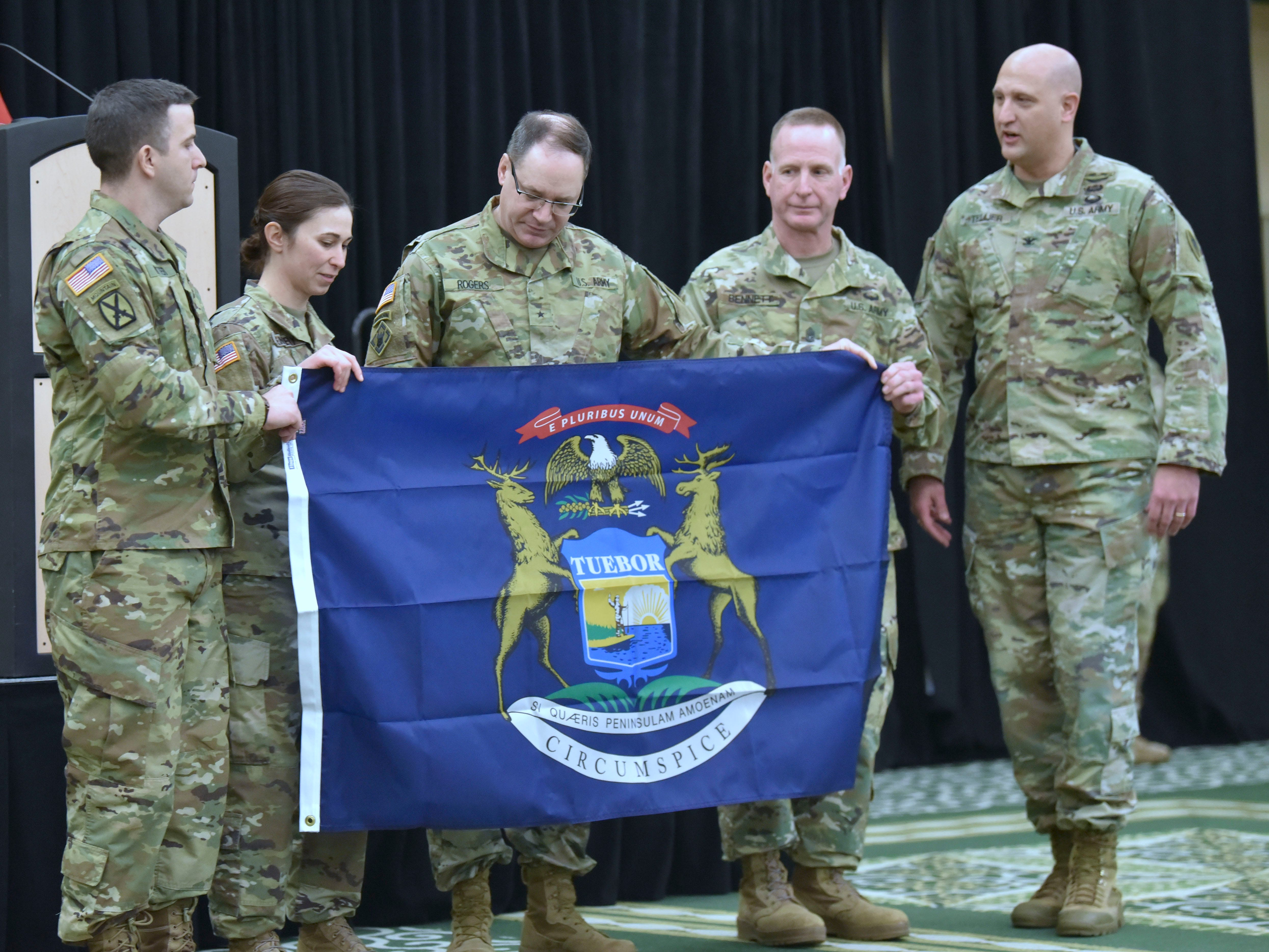 (L-R): 1st Sgt. Jason Ritter, Captain Andrea Kennedy, Brigadier General Paul Rogers, Command Sgt. Major Jay Bennett and Colonel Mark Tellier pose with the Michigan flag that was presented to the 1171st Medical Company, Area Support (MCAS) unit for them fly during their oversees deployment at a ceremony at EMU, Saturday morning, January 5, 2019.