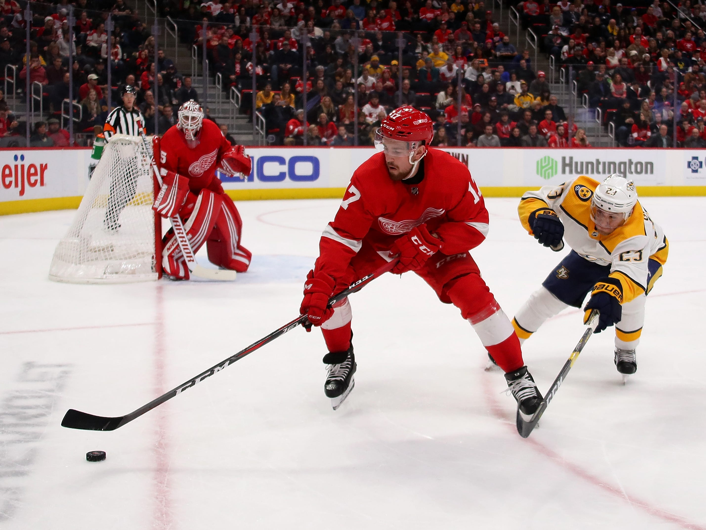 Red Wings' Filip Hronek (17) tries to control the puck next to Predators' Rocco Grimaldi (23) during the first period.