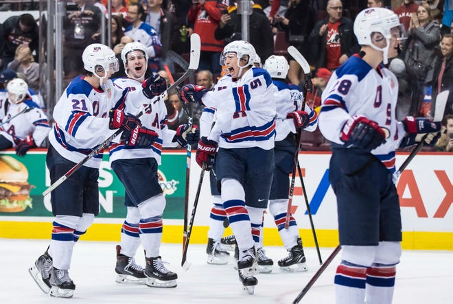 United States' Noah Cates, Mattias Samuelsson and Jason Robertson and Joel Farabee, right front, celebrate after the U.S. defeated Russia during a world junior hockey championships semifinal on Friday.