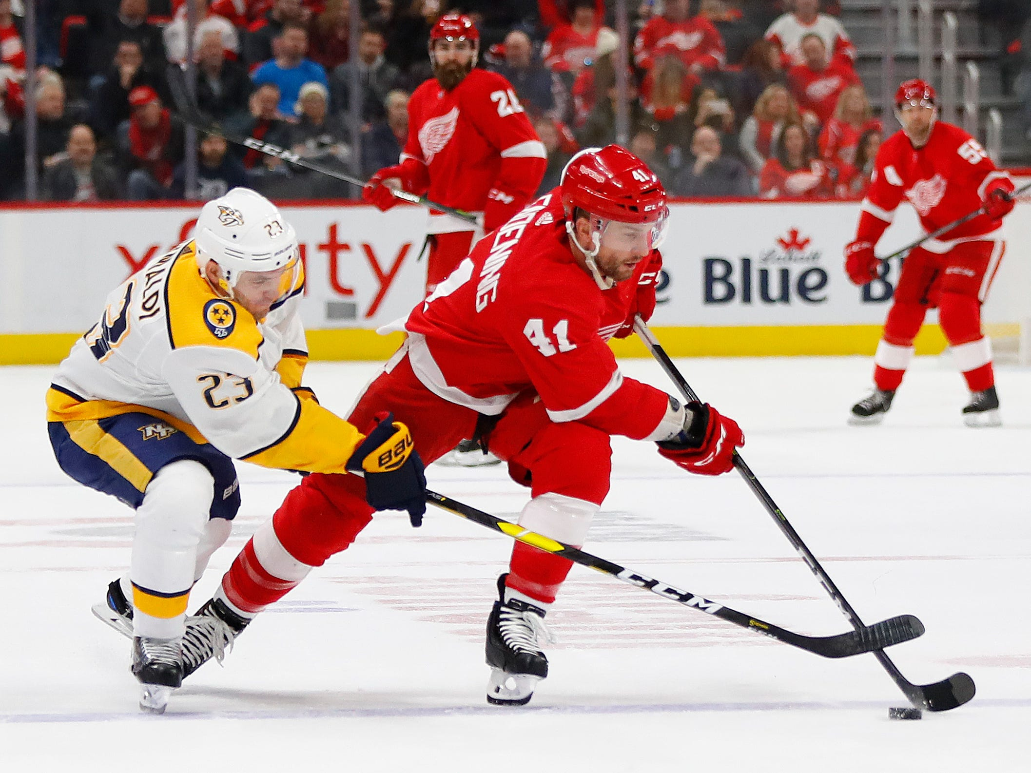 Nashville Predators center Rocco Grimaldi (23) tries to steal the puck from Detroit Red Wings center Luke Glendening (41) in the first period.