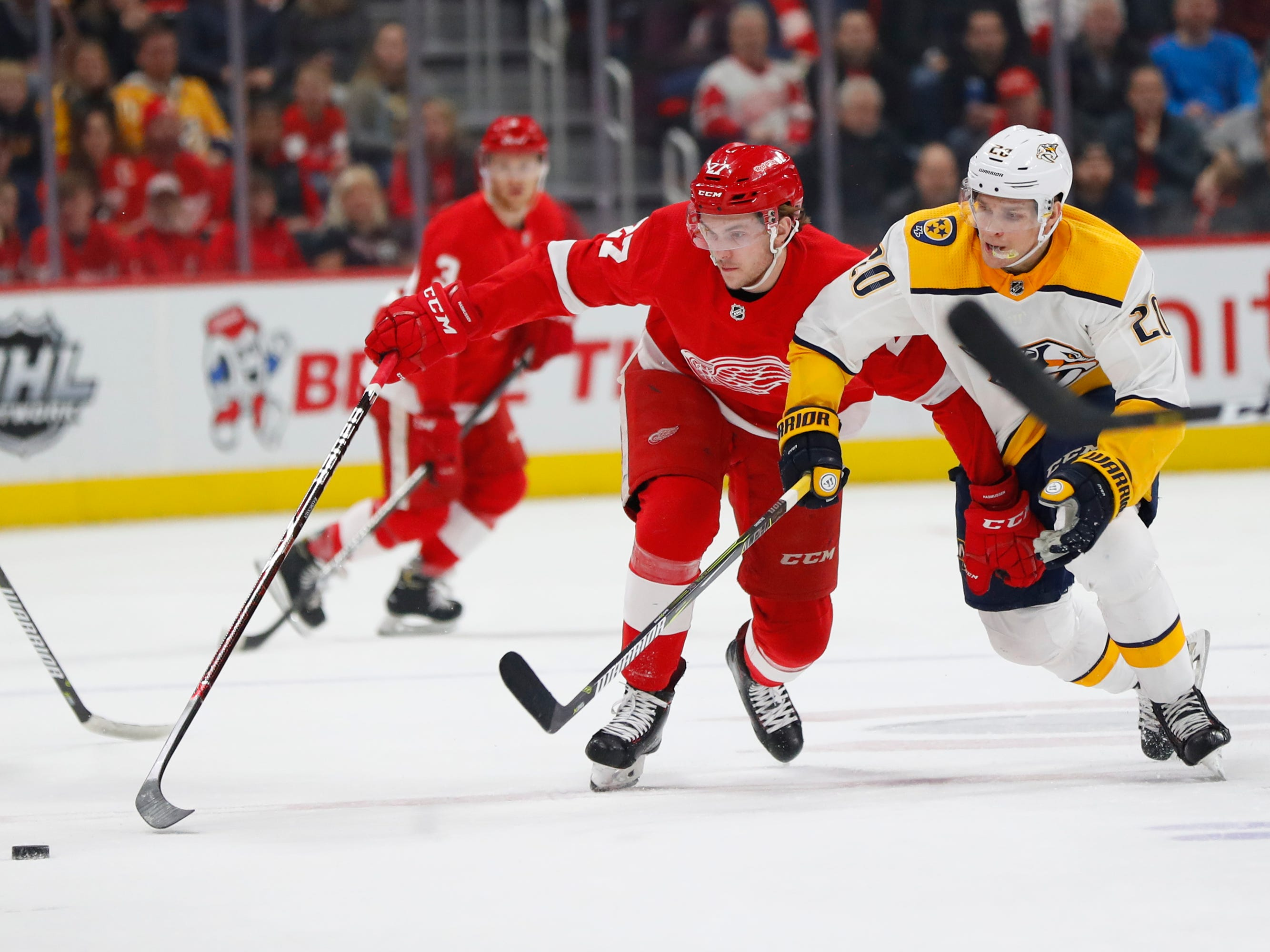 Detroit Red Wings center Michael Rasmussen (27) and Nashville Predators right wing Miikka Salomaki (20) battle for the puck in the first period of an NHL hockey game Friday, Jan. 4, 2019, in Detroit. (AP Photo/Paul Sancya)