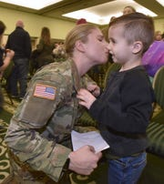 2nd Lt. Emma Smith gives a kiss to her nephew Madden Menchinger, 4.