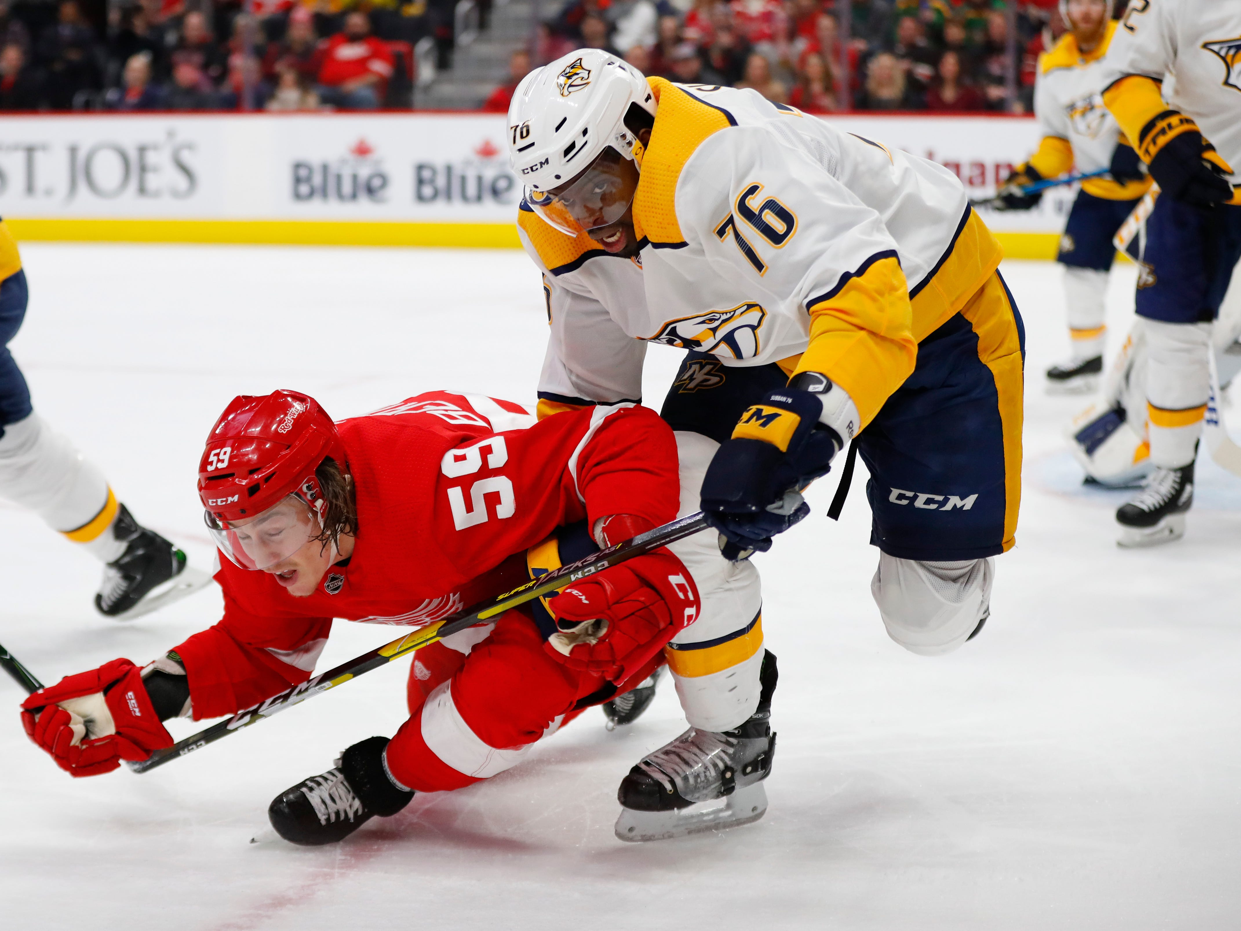 Nashville Predators defenseman P.K. Subban (76) takes down Detroit Red Wings left wing Tyler Bertuzzi (59) while chasing the puck in the first period.